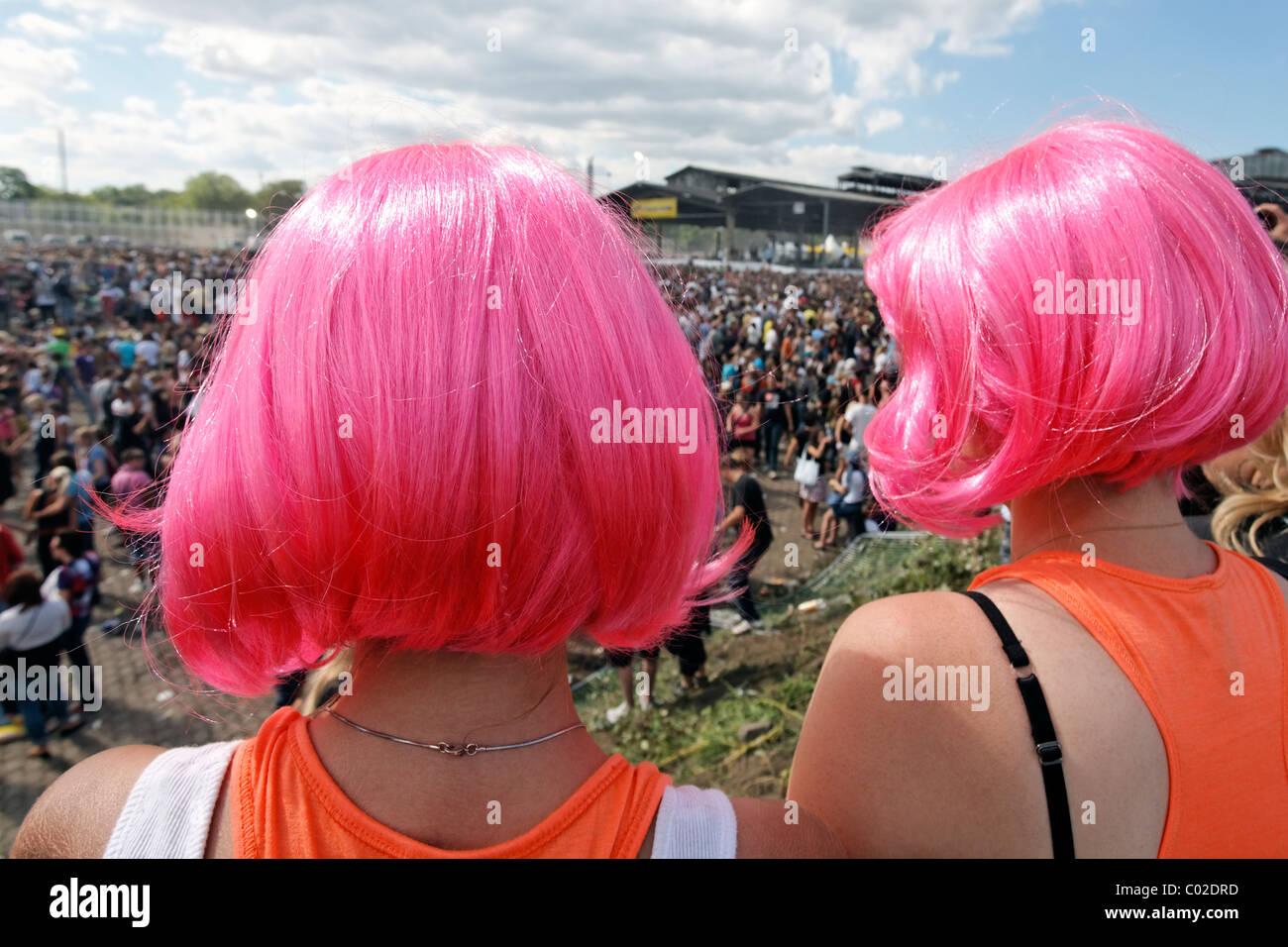 Deux jeunes femmes ravers portant des perruques whacky regarder la foule, Loveparade 2010, Duisbourg, Rhénanie Photo Stock