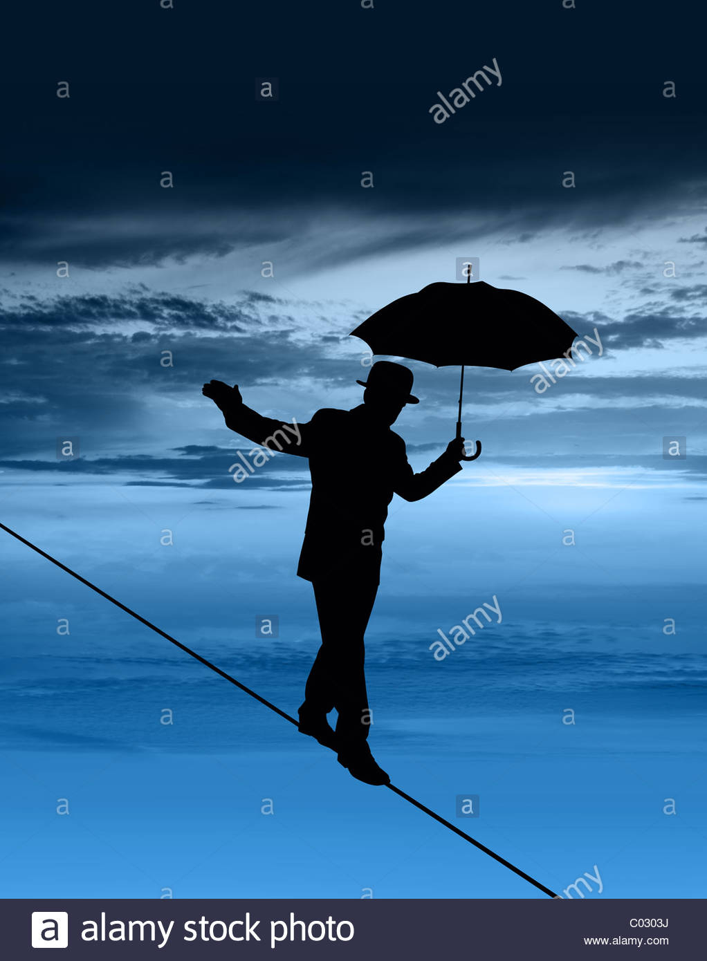 Silhouette of businessman on tightrope Photo Stock