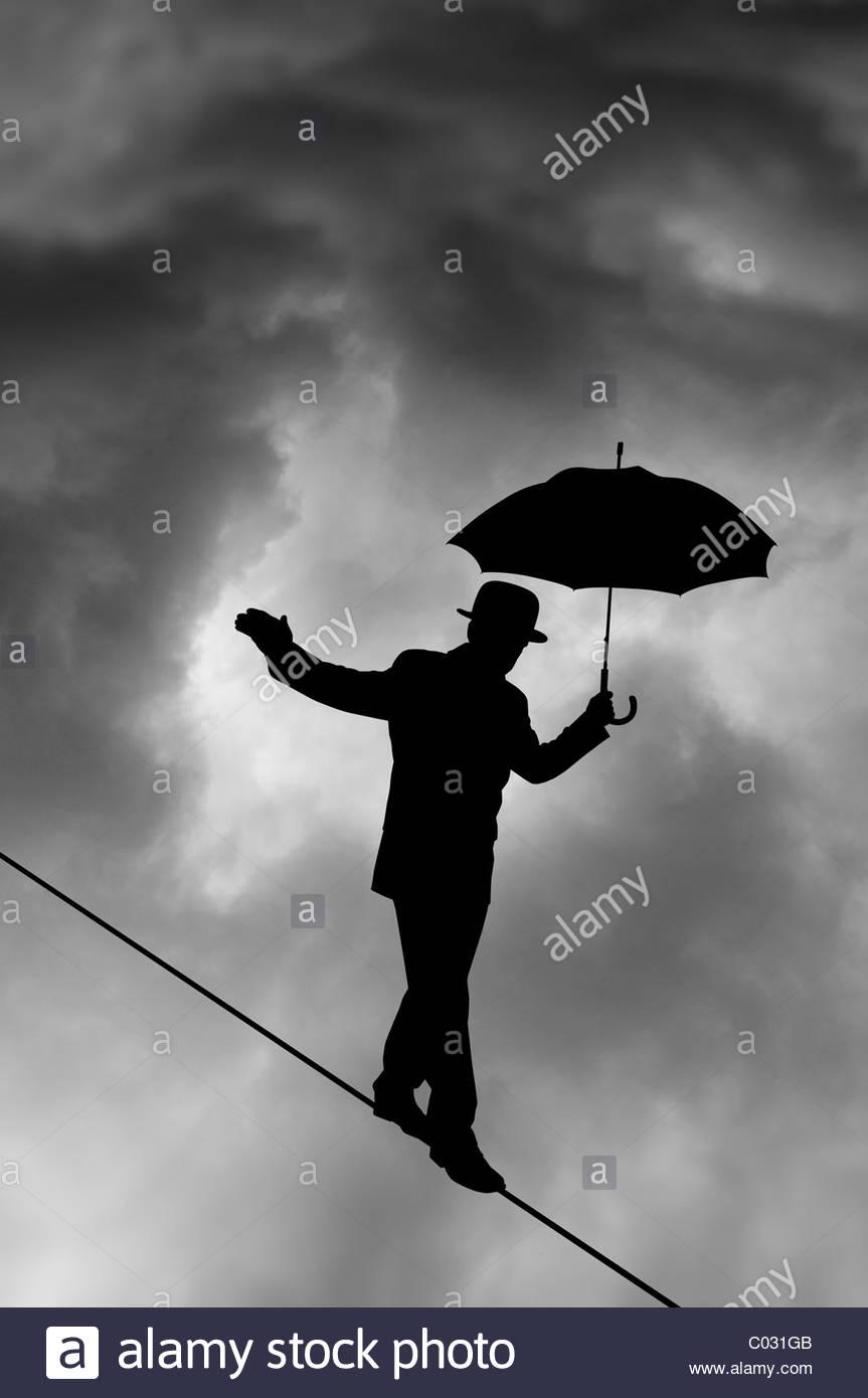 Silhouette funambule contre nuage noir Photo Stock