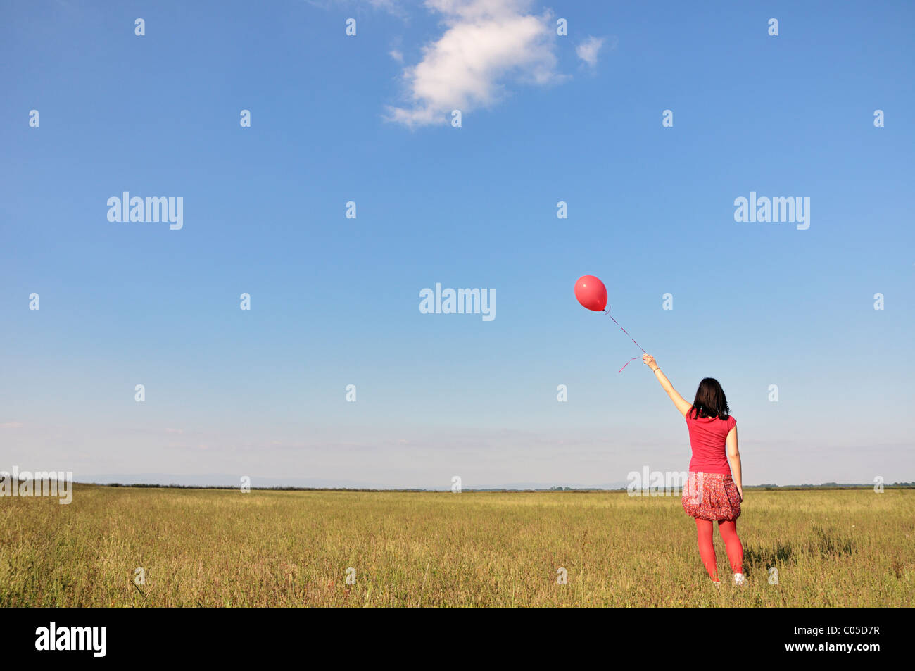 Happy young woman holding red balloon Photo Stock