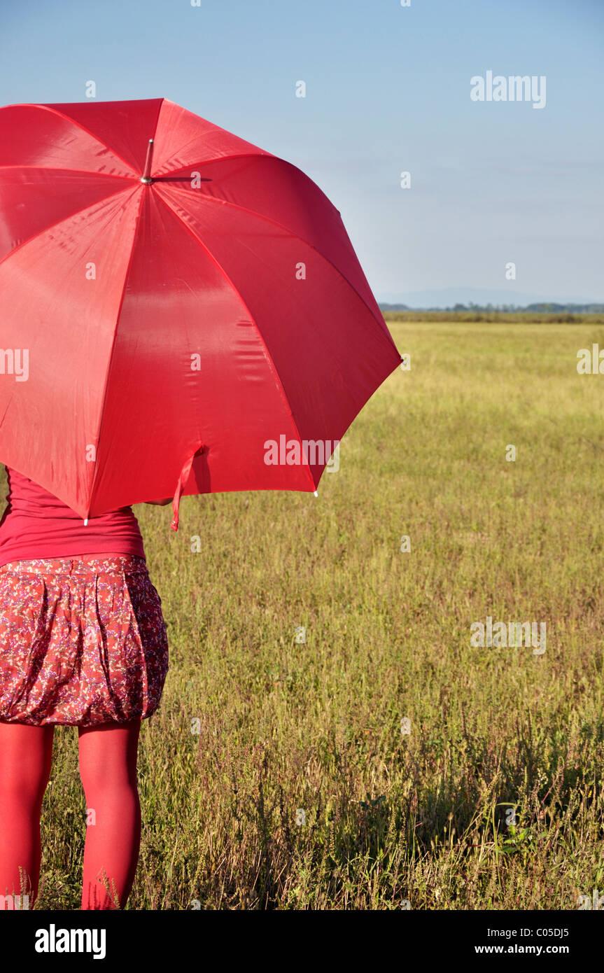 Jeune femme tenant parapluie rouge Photo Stock