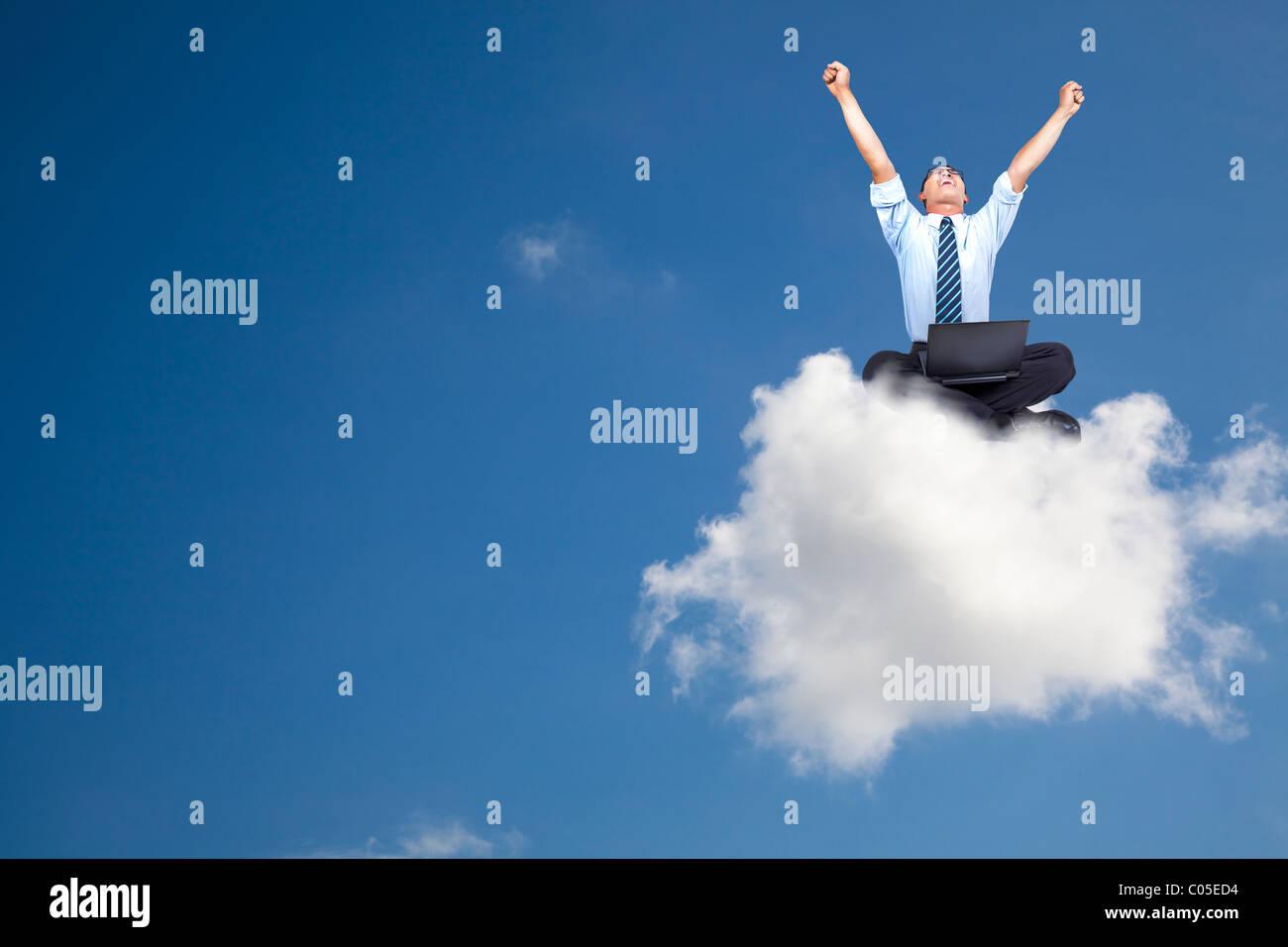 Jeune homme d'affaires avec ordinateur assis sur le nuage Photo Stock