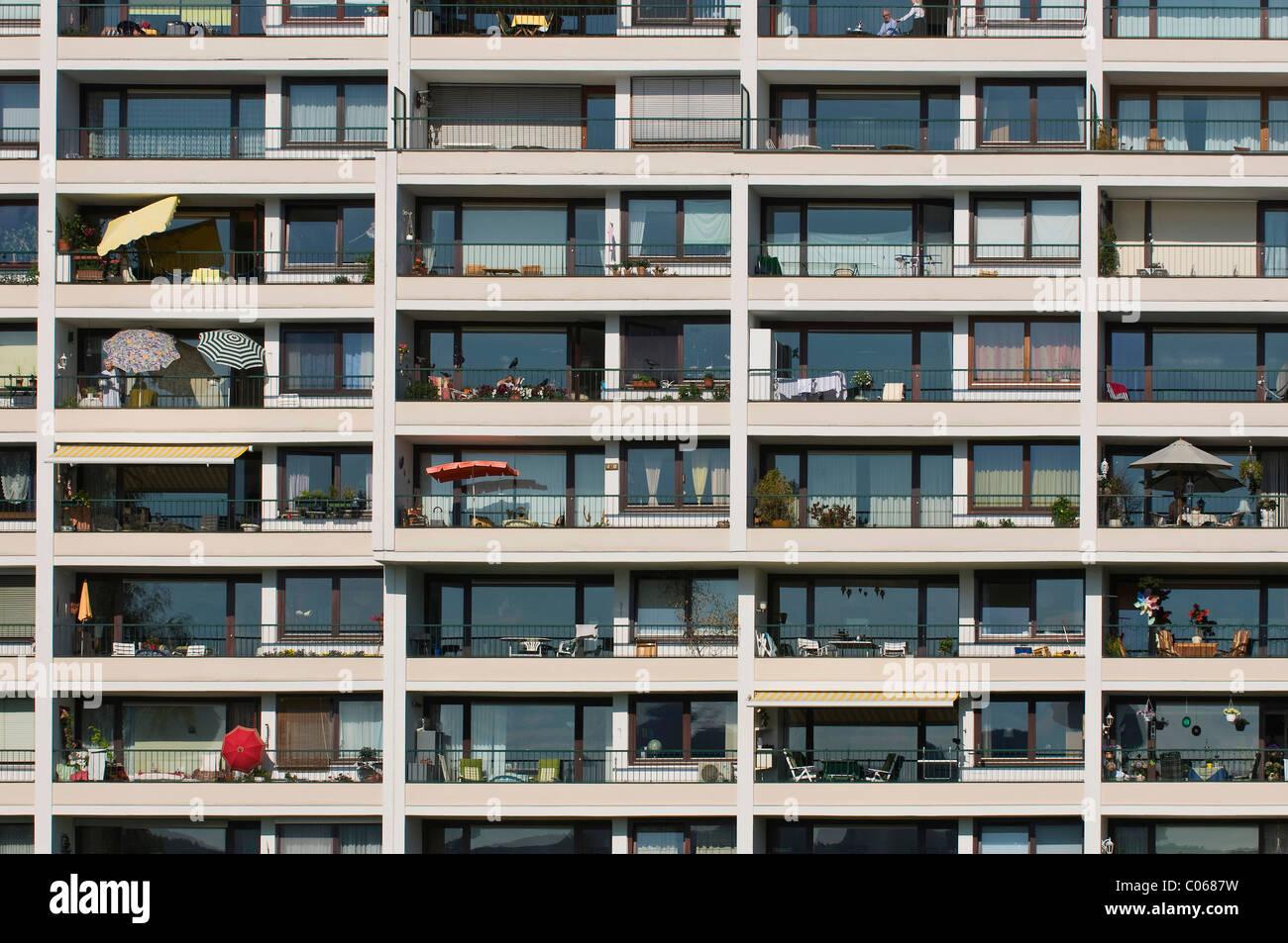 Façade de maison, nombreux balcons avec parasols et meubles Photo Stock