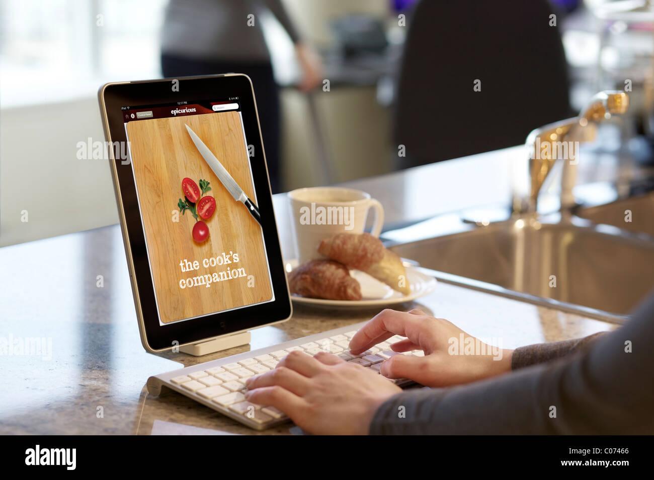 Recette de cuisine femme parcourt avec l'application de cuisine Epicurious iPad Photo Stock