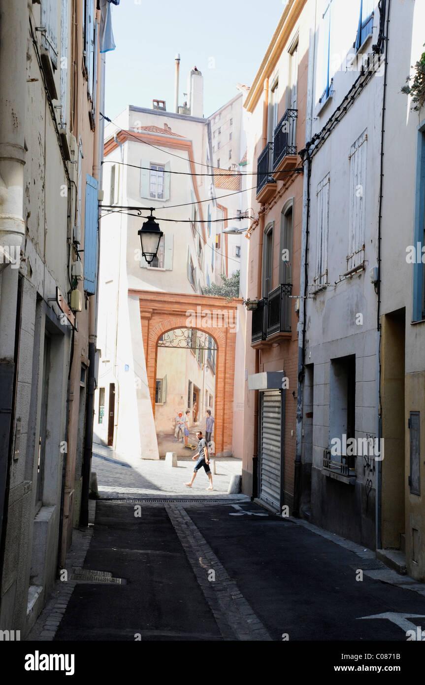 Un homme passe devant une peinture murale 3 d de maisons dans une rue de Perpignan, France Photo Stock