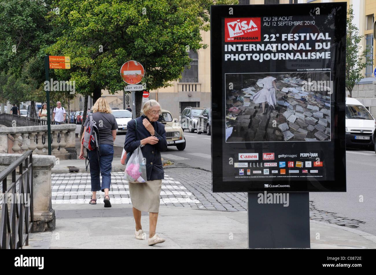 Une vieille dame passe une annonce photographique pour une photo festival en France, Perpignan. Visa pour l'image. Photo Stock