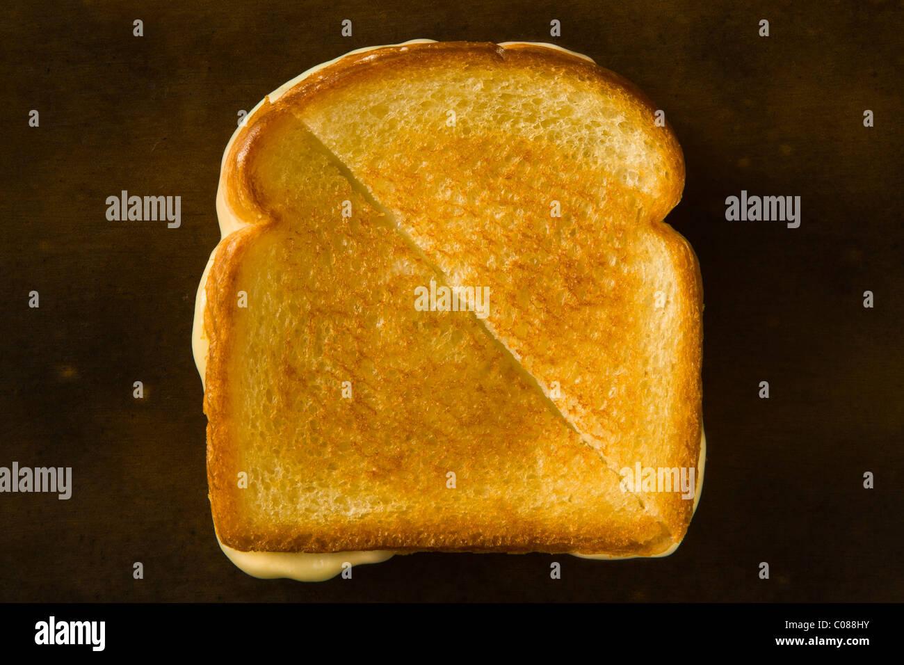 Un sandwich au fromage coupé en deux en diagonale en tirant le fromage sur une table en bois Photo Stock