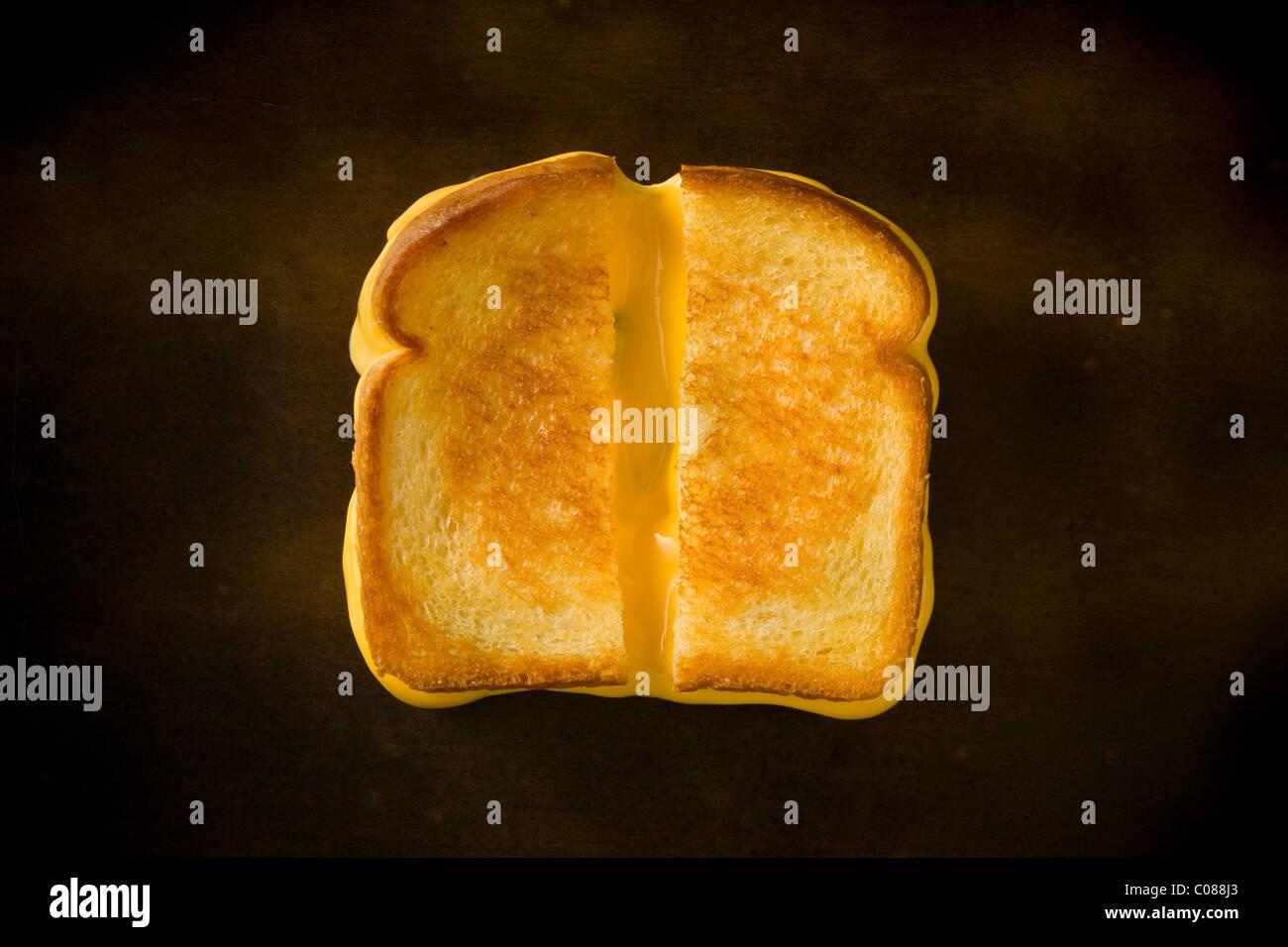 Un sandwich au fromage coupé en deux en tirant le fromage sur une table en bois Photo Stock