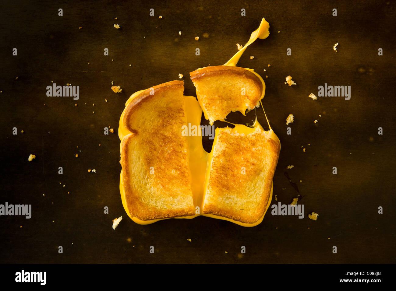 Un sandwich au fromage coupé en deux et avec le coin supérieur droit de rupture tirant le fromage sur Photo Stock