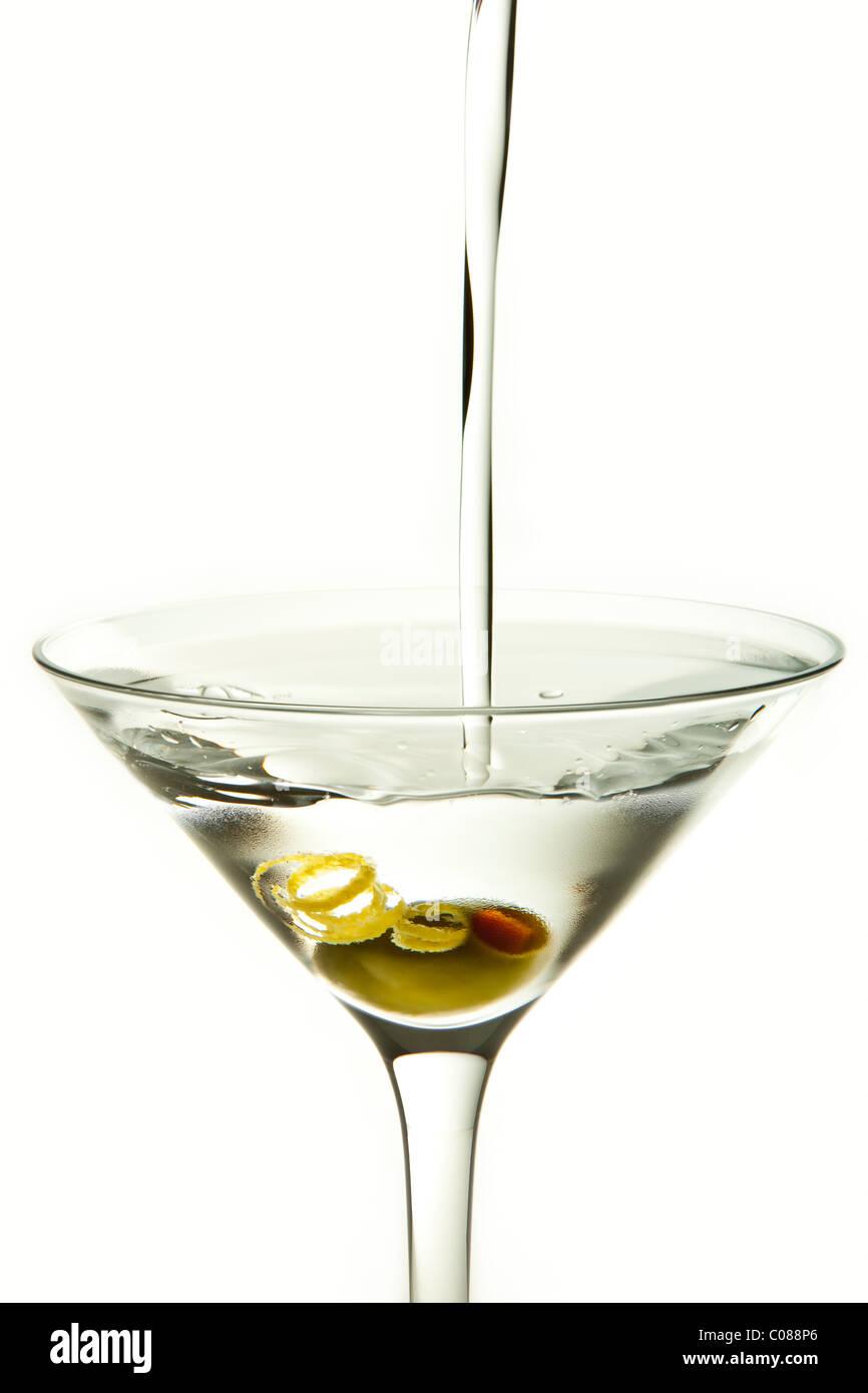 Un verre de cocktail Martini Olive et garnir avec le verser sur un fond blanc. Photo Stock