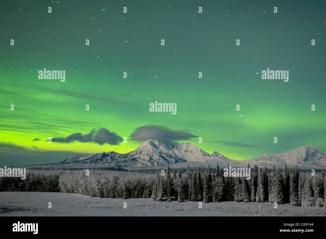Aurora Borealis vert s'allume le ciel nocturne au-dessus de Mt. Sanford et de Mt. Drum dans les monts Wrangell, Photo Stock