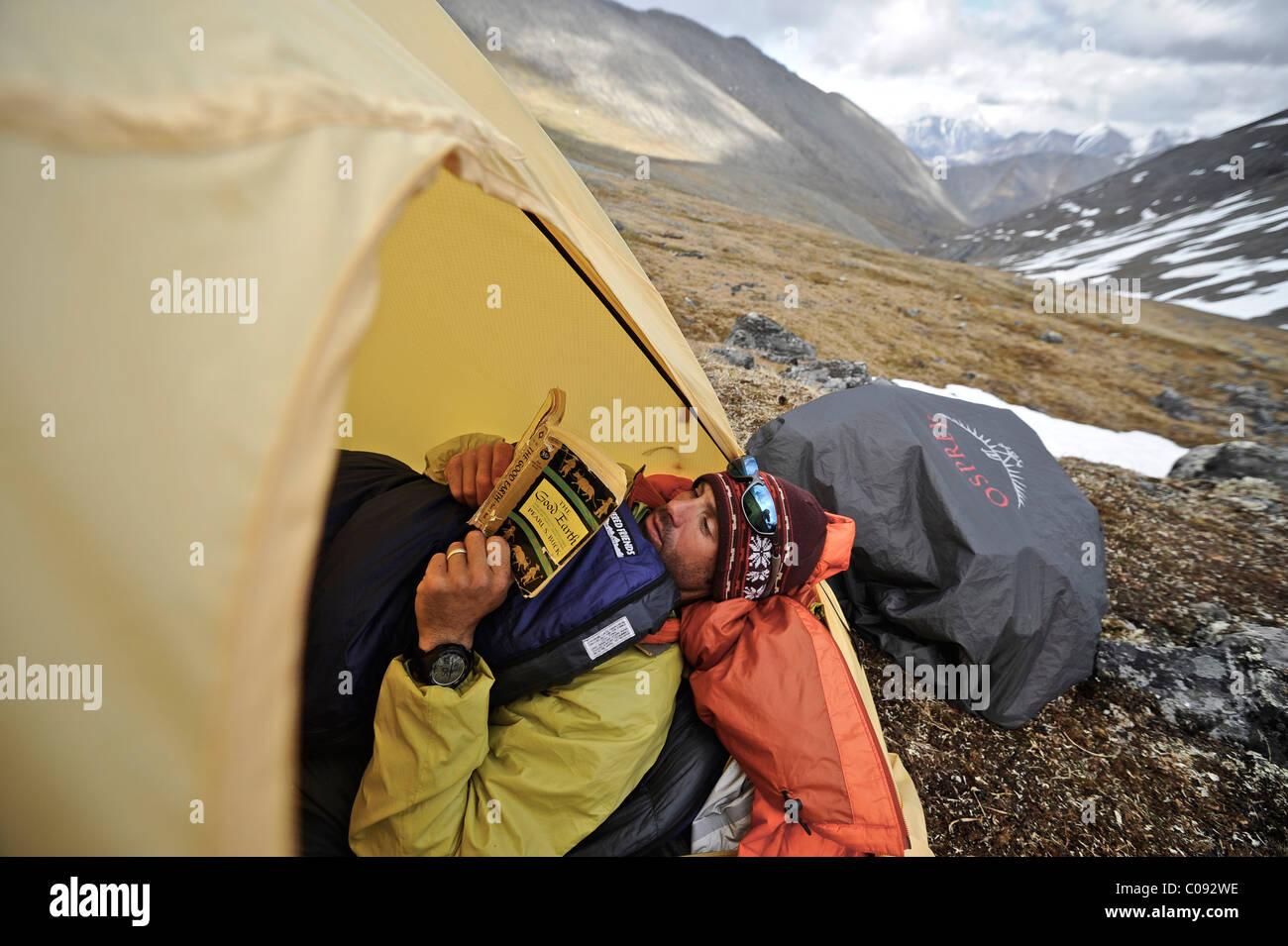 Backpacker lit un livre à l'intérieur d'une tente et attend le mauvais temps à un camp alpin Photo Stock