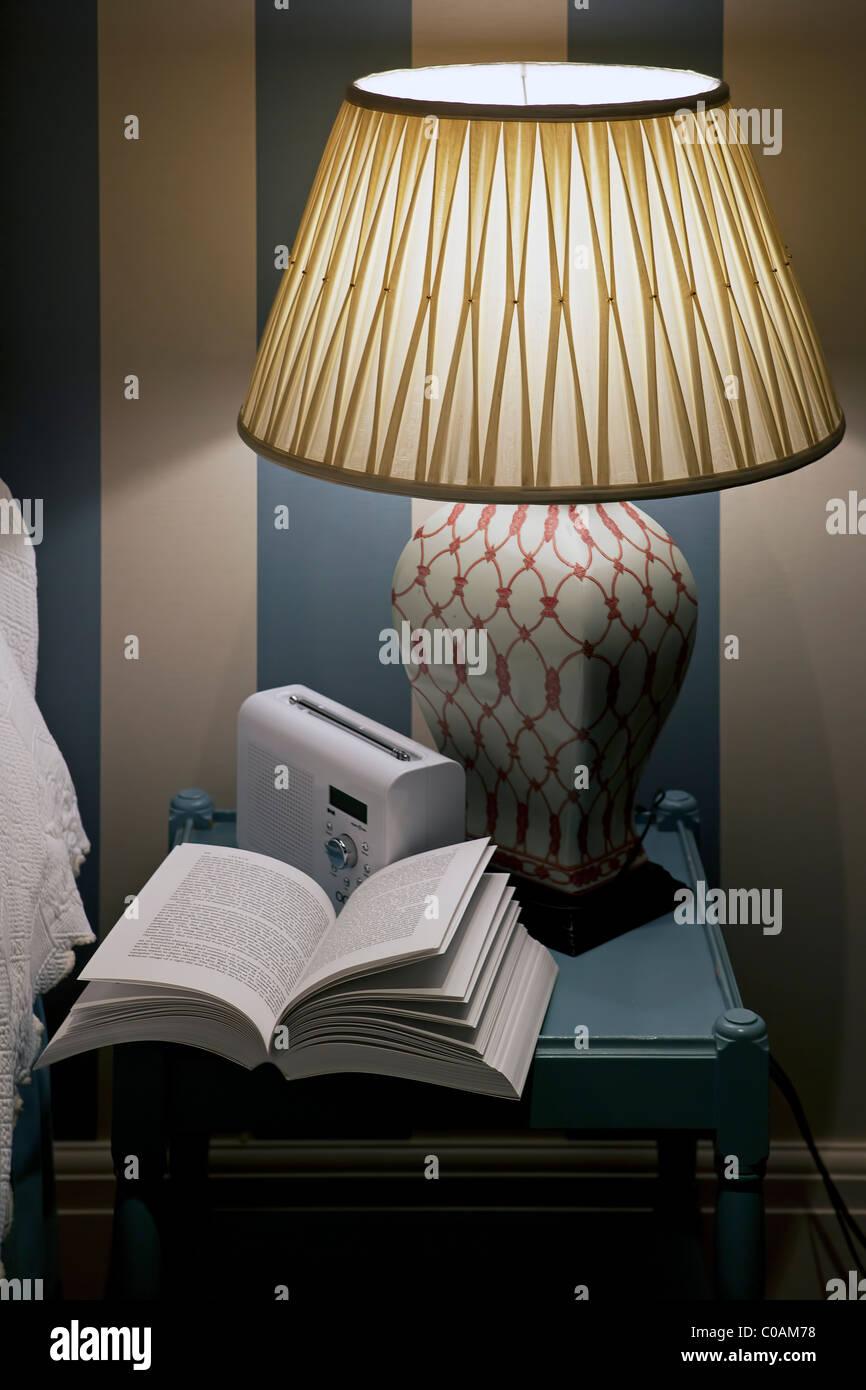 Table de chevet avec lampe, radio et livre ouvert Photo Stock