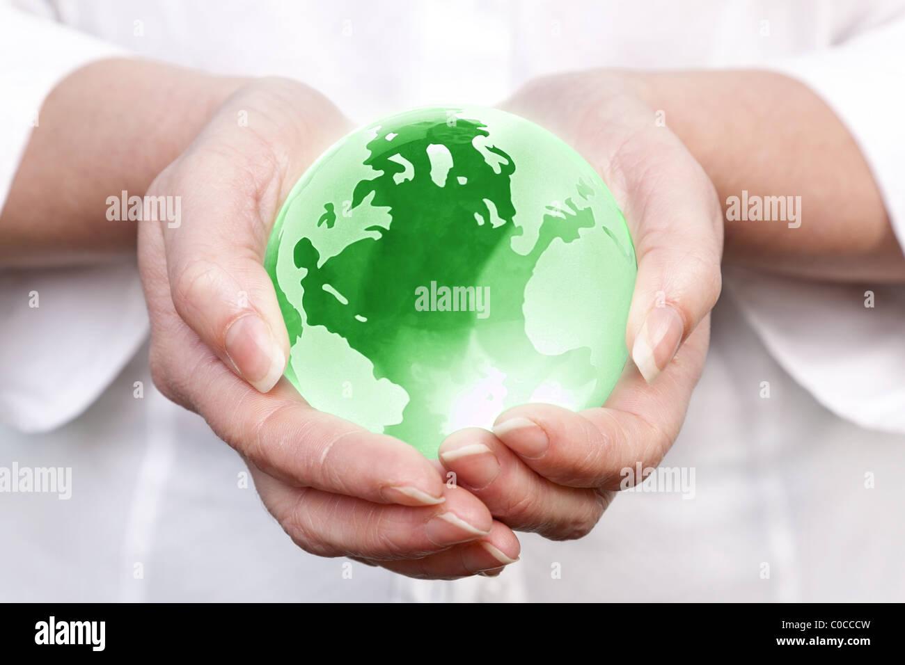 Photo d'une femme tenant un globe en verre verte dans ses mains, concept de droit pour l'environnement mondial Photo Stock