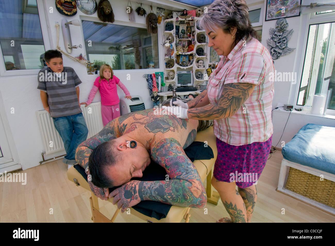 Une femme tatoueur travaille sur un dessin sur son mari est de retour, regardée par leurs deux enfants s'ennuyer. Photo Stock