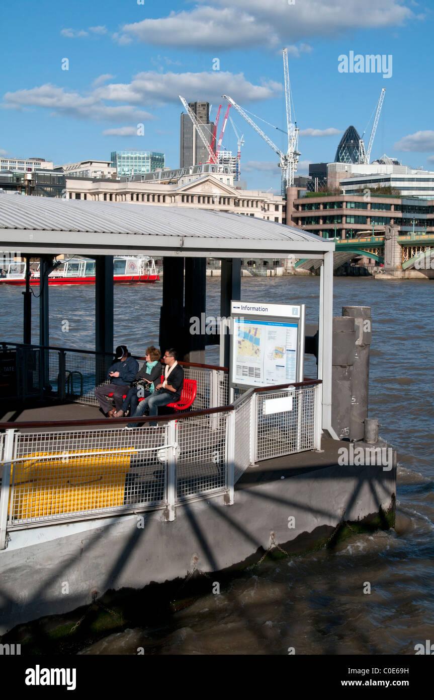 Les touristes l'EMBARQUEMENT FERRY LE LONG DE LA RIVIÈRE THAMES AVEC CITY DE LONDRES EN ARRIÈRE-PLAN Photo Stock