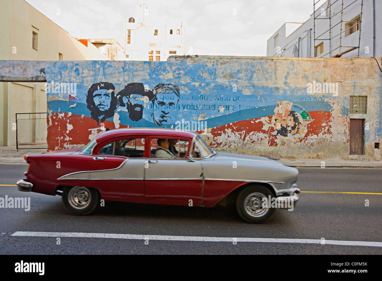 Un vieux American 1950 conduite automobile passé une fresque peinte Che Guevara à La Havane Cuba Banque D'Images