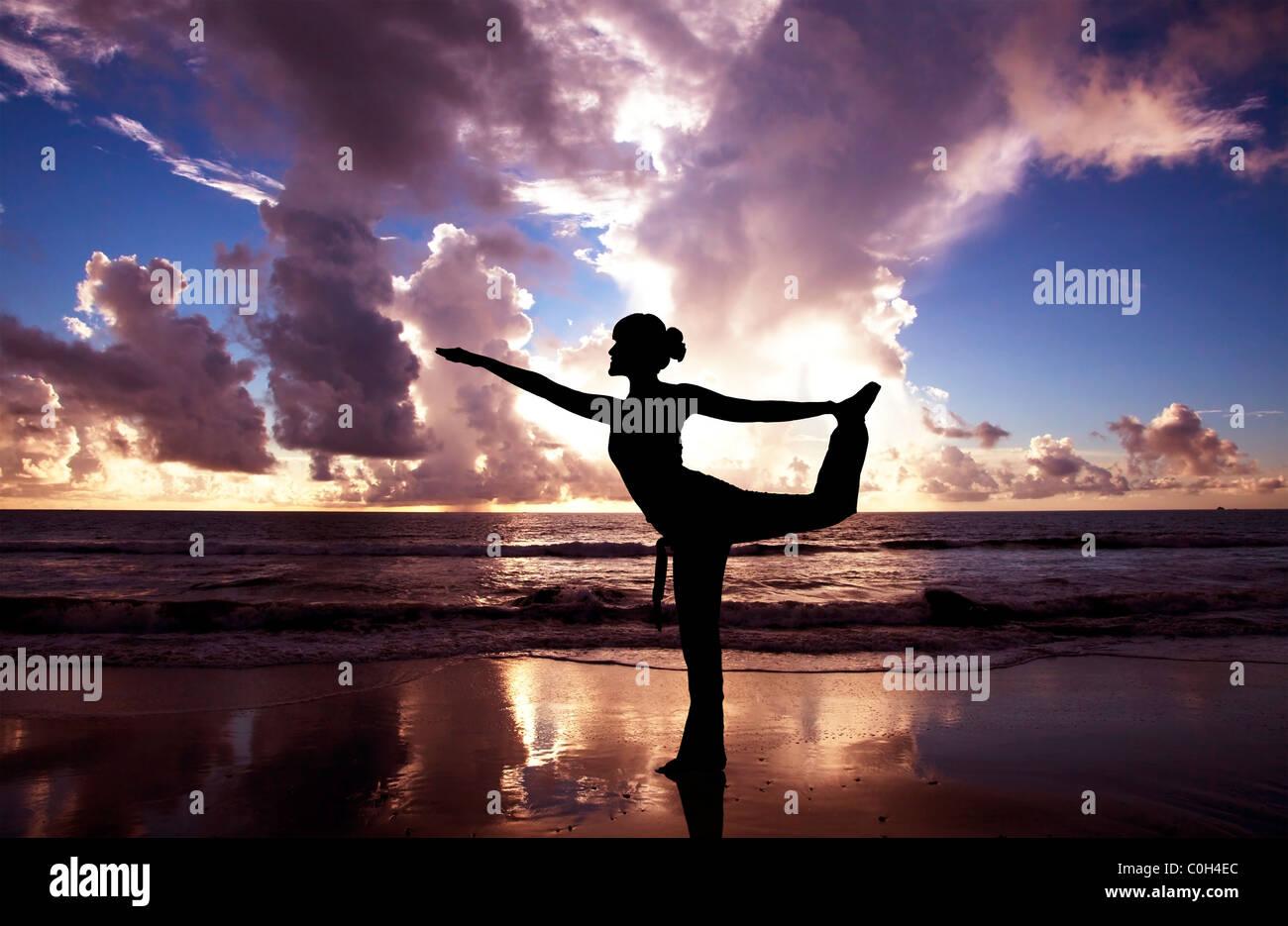 Yoga woman sur la belle plage au lever du soleil Photo Stock