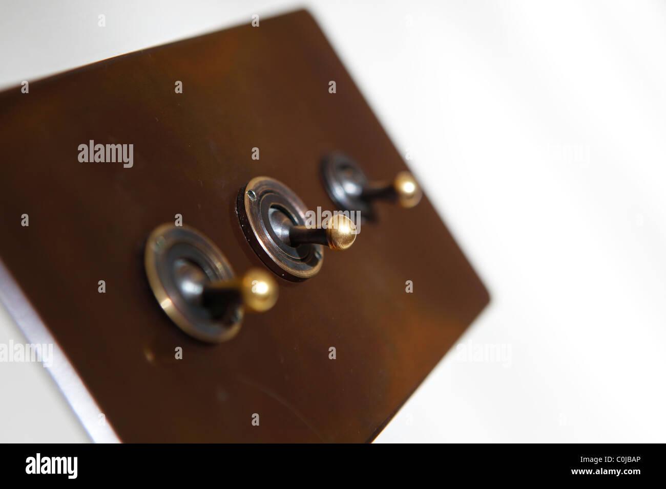 Interrupteur d'éclairage traditionnel dans une chambre sur un mur blanc Photo Stock