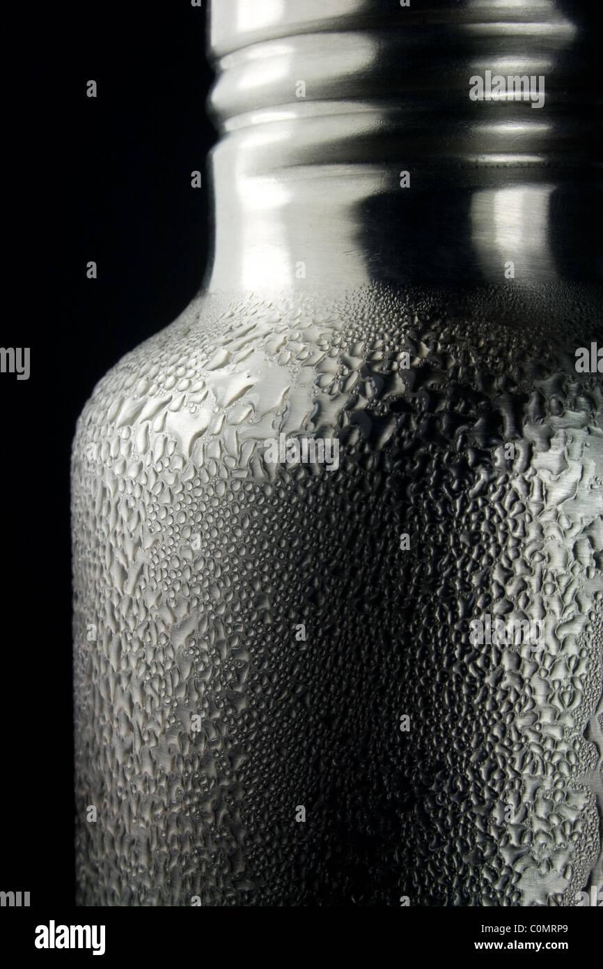 La condensation de l'eau tombe sur une bouteille d'eau froide Banque D'Images