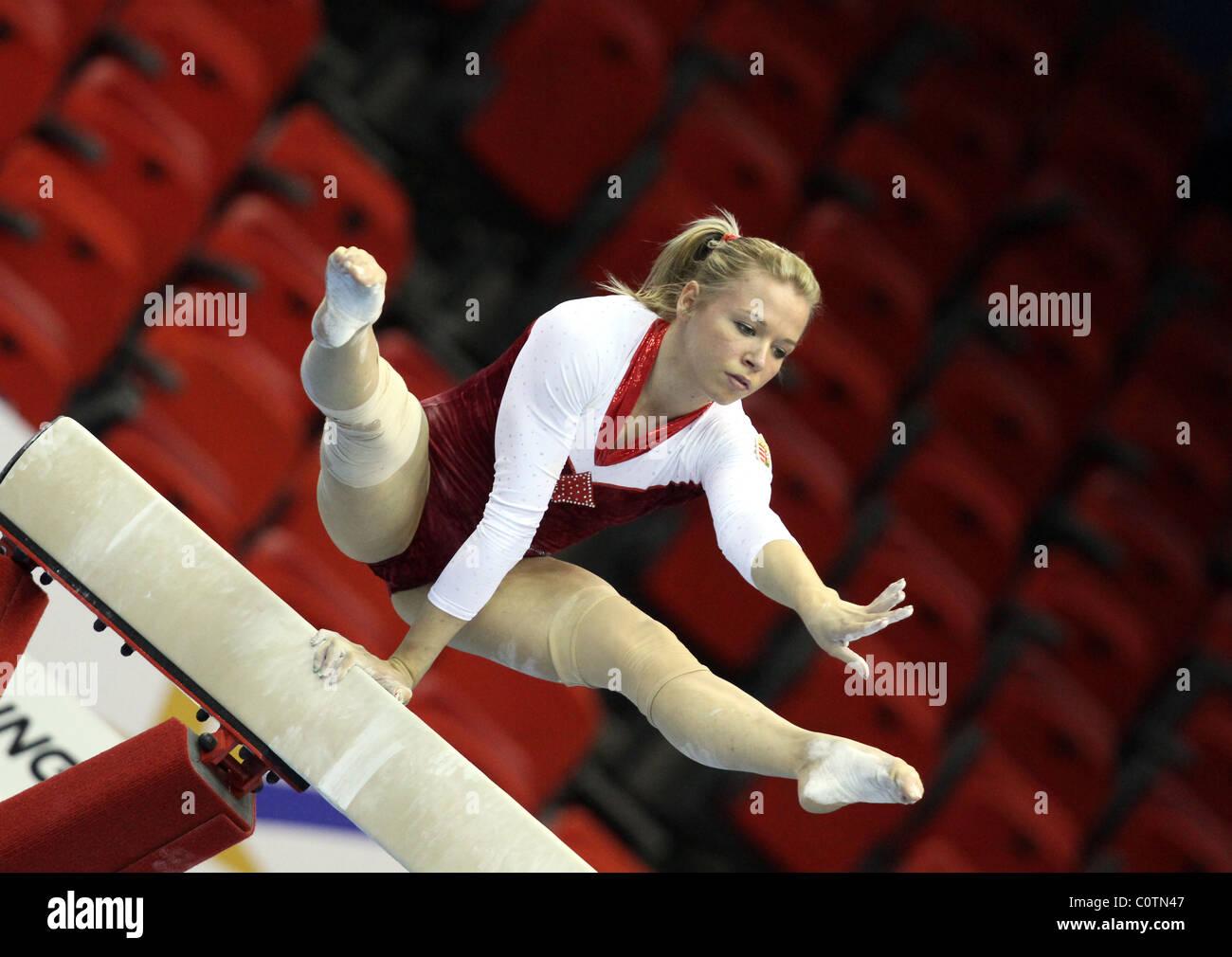Gymnaste effectue un ATR à l'aide d'un bras sur le faisceau à un concours de gymnastique Photo Stock