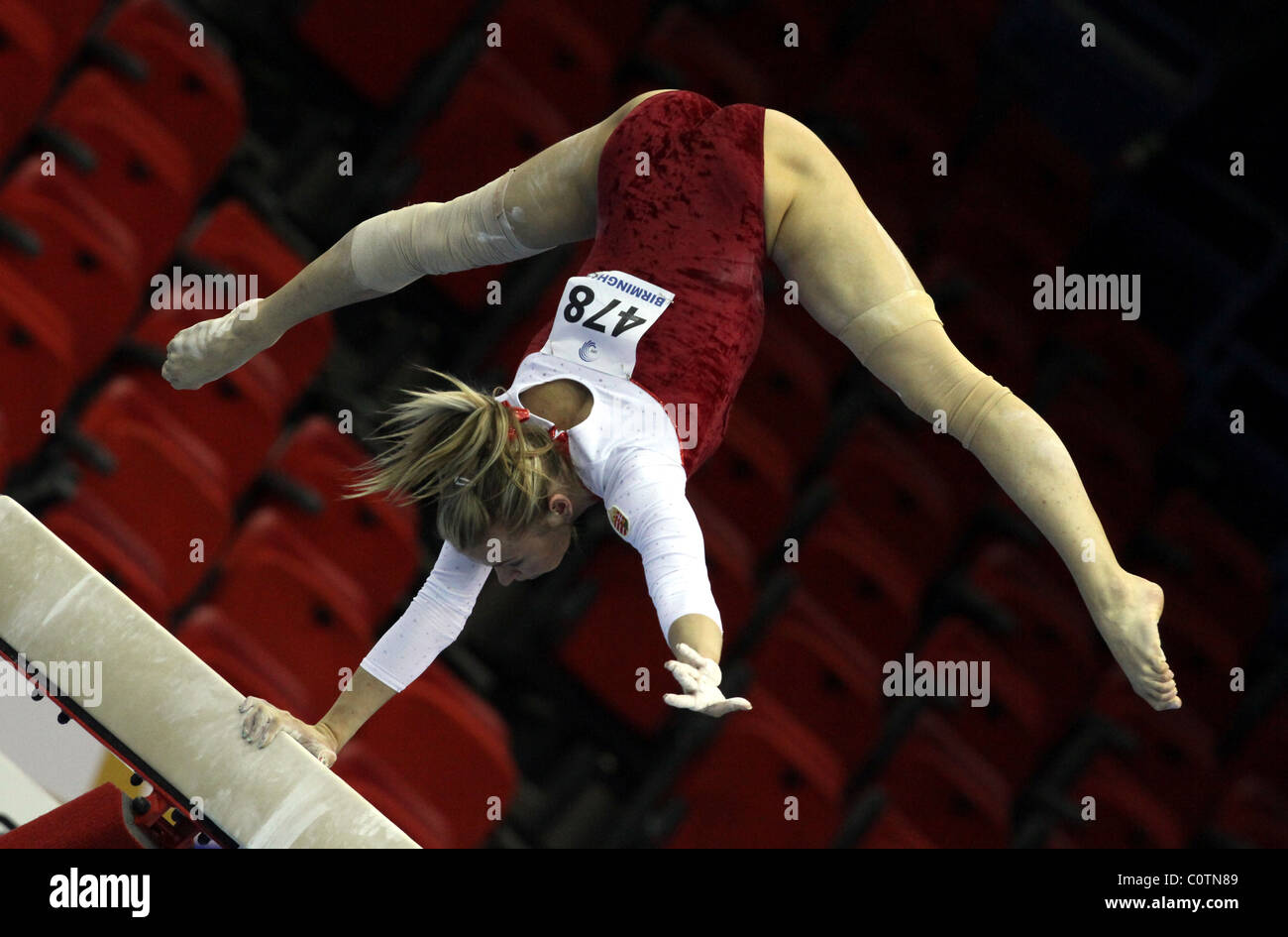 Gymnaste effectue un ATR à l'aide d'un bras sur le faisceau à un concours de gymnastique Banque D'Images
