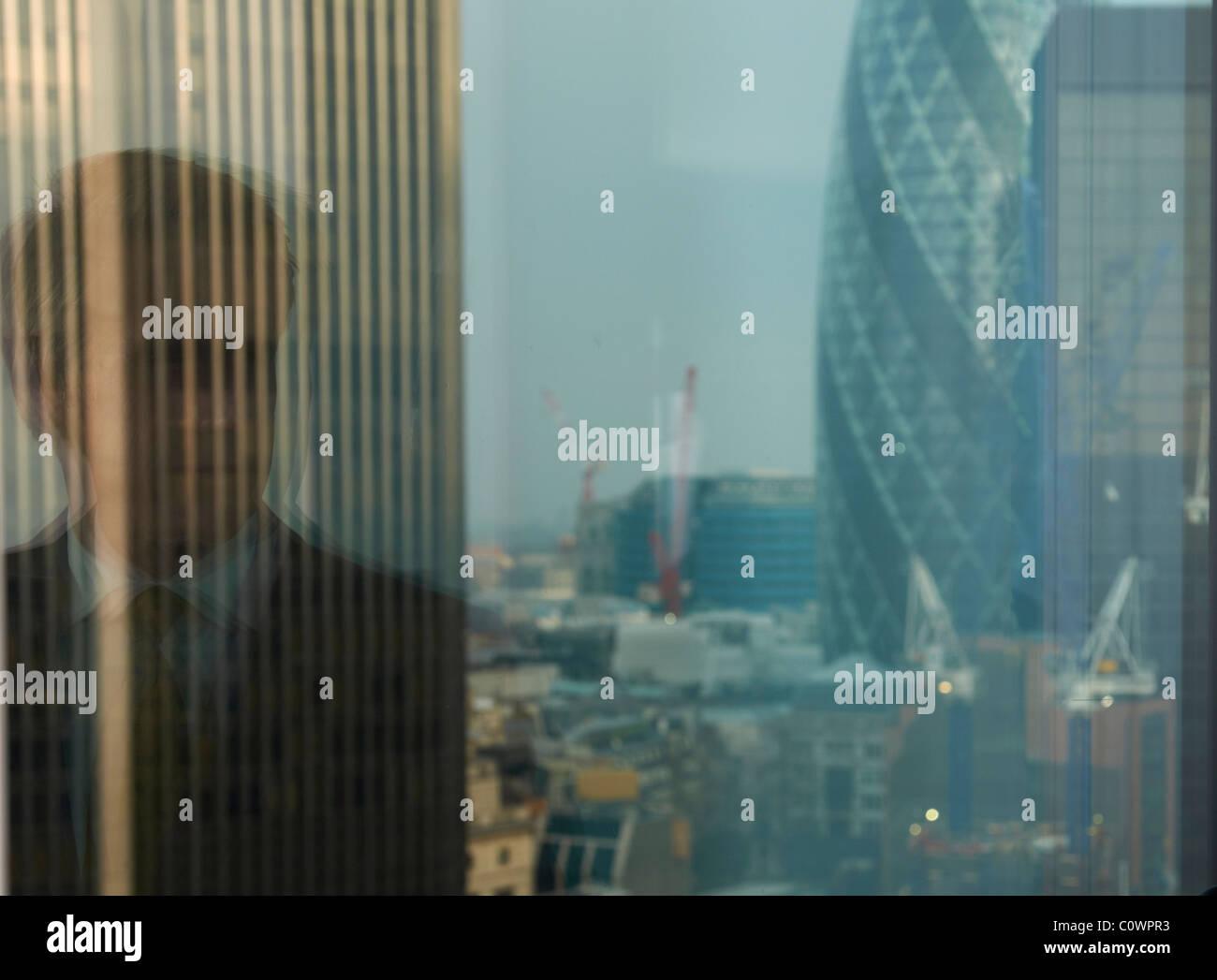 Reflet de l'homme d'affaires dans la fenêtre avec la vue du quartier de la city de Londres en arrière Photo Stock