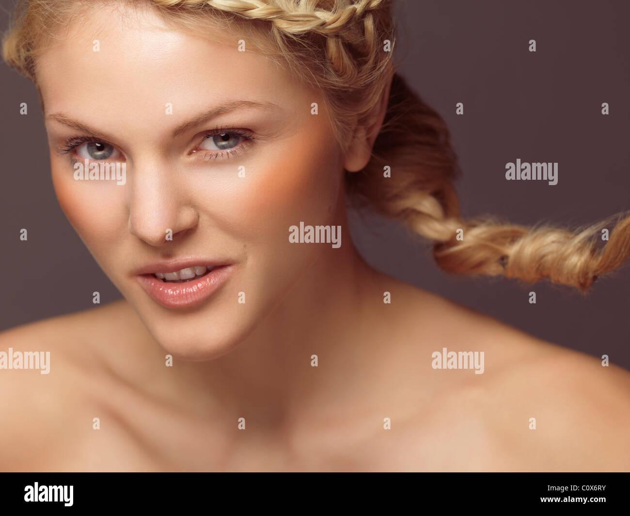 Portrait de beauté d'une jeune femme souriante avec une tresse et blush orange Banque D'Images