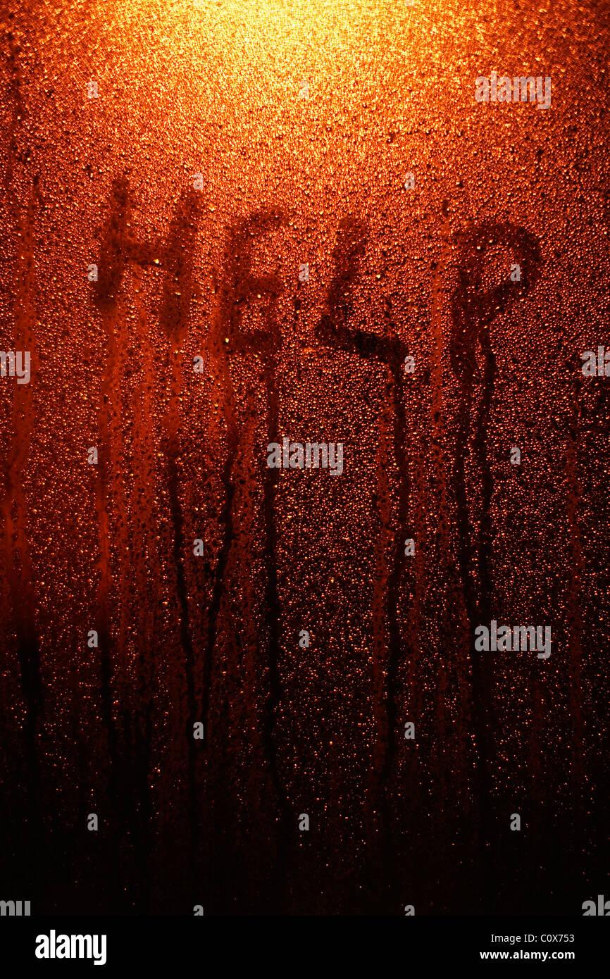 Aide - bout de doigt écrit sur la fenêtre avec la condensation. Photo Stock