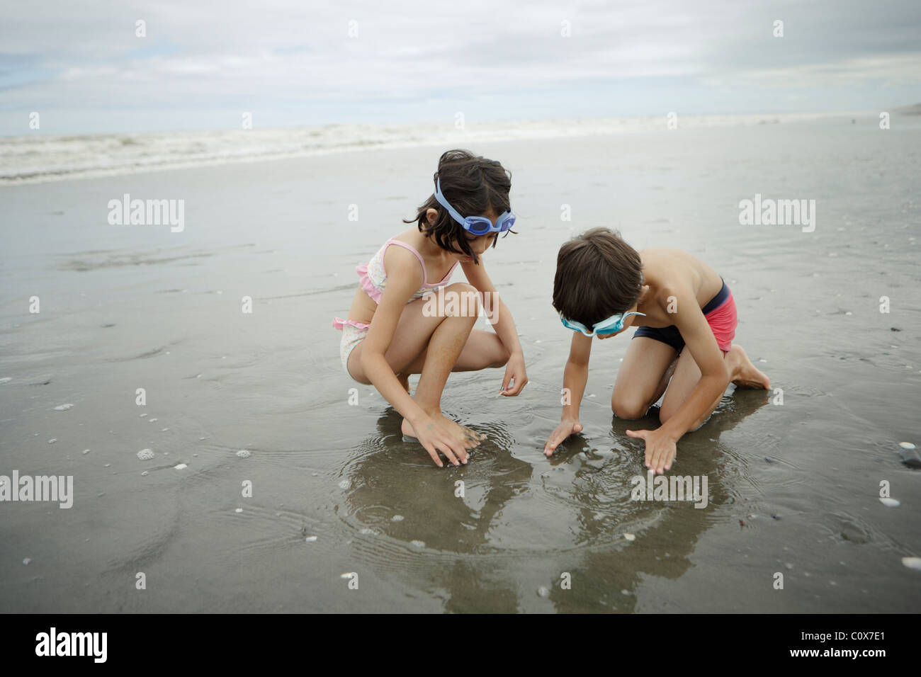 Frère et sœur, mixed race, jouer dans la mer. Manawatu, Nouvelle-Zélande. Banque D'Images