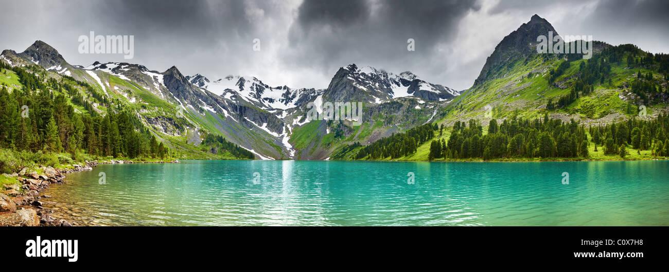 Paysage de montagne avec lac turquoise et ciel nuageux Photo Stock
