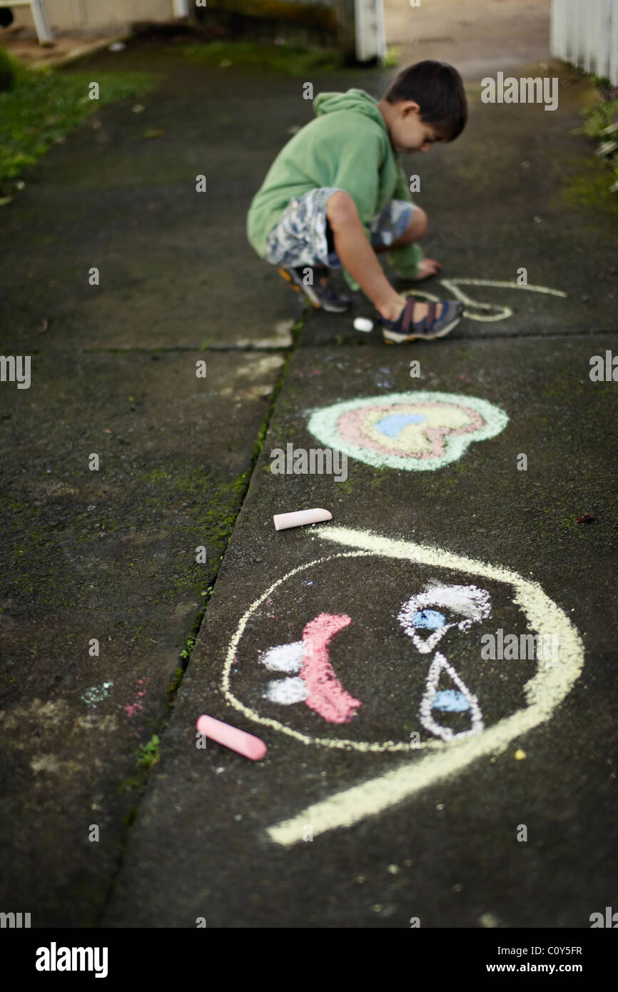 Boy drawing sur chemin avec de la craie Photo Stock