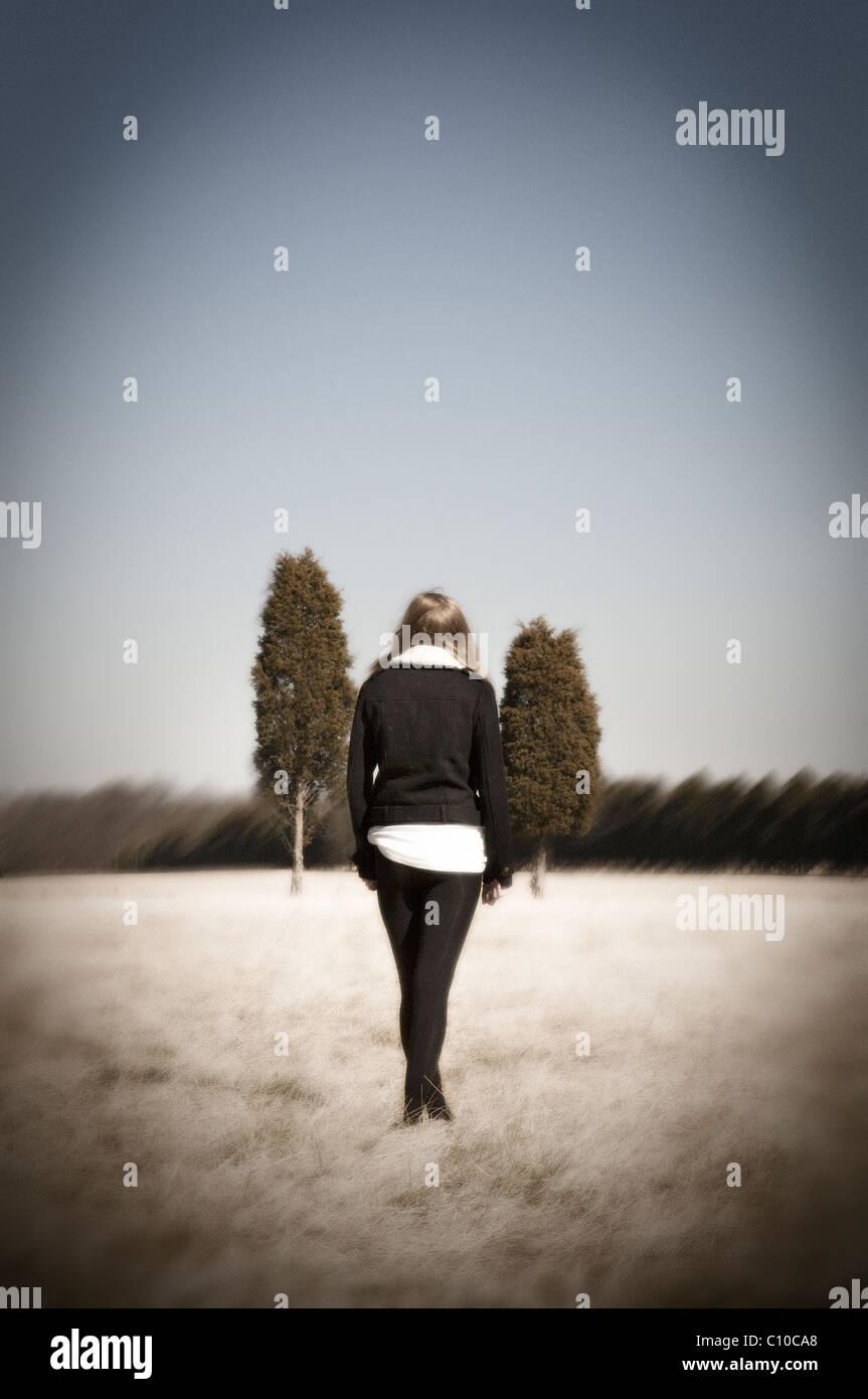 Une adolescente se tenir dans un champ portant des collants noirs et un manteau noir avec deux arbres au loin. Photo Stock