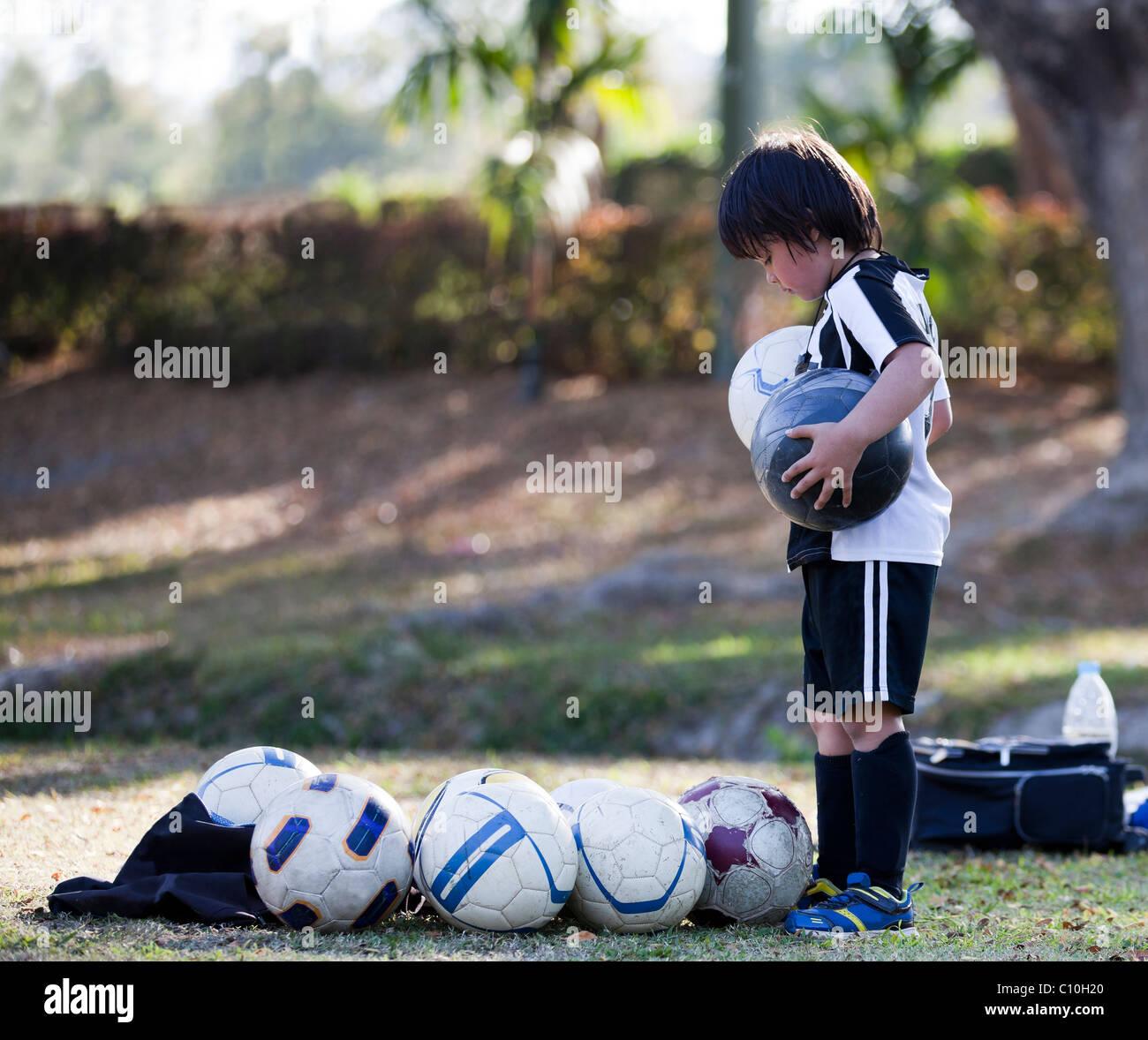 Un beau jeune garçon de six ans, compte le nombre de ballons qu'il a. Banque D'Images