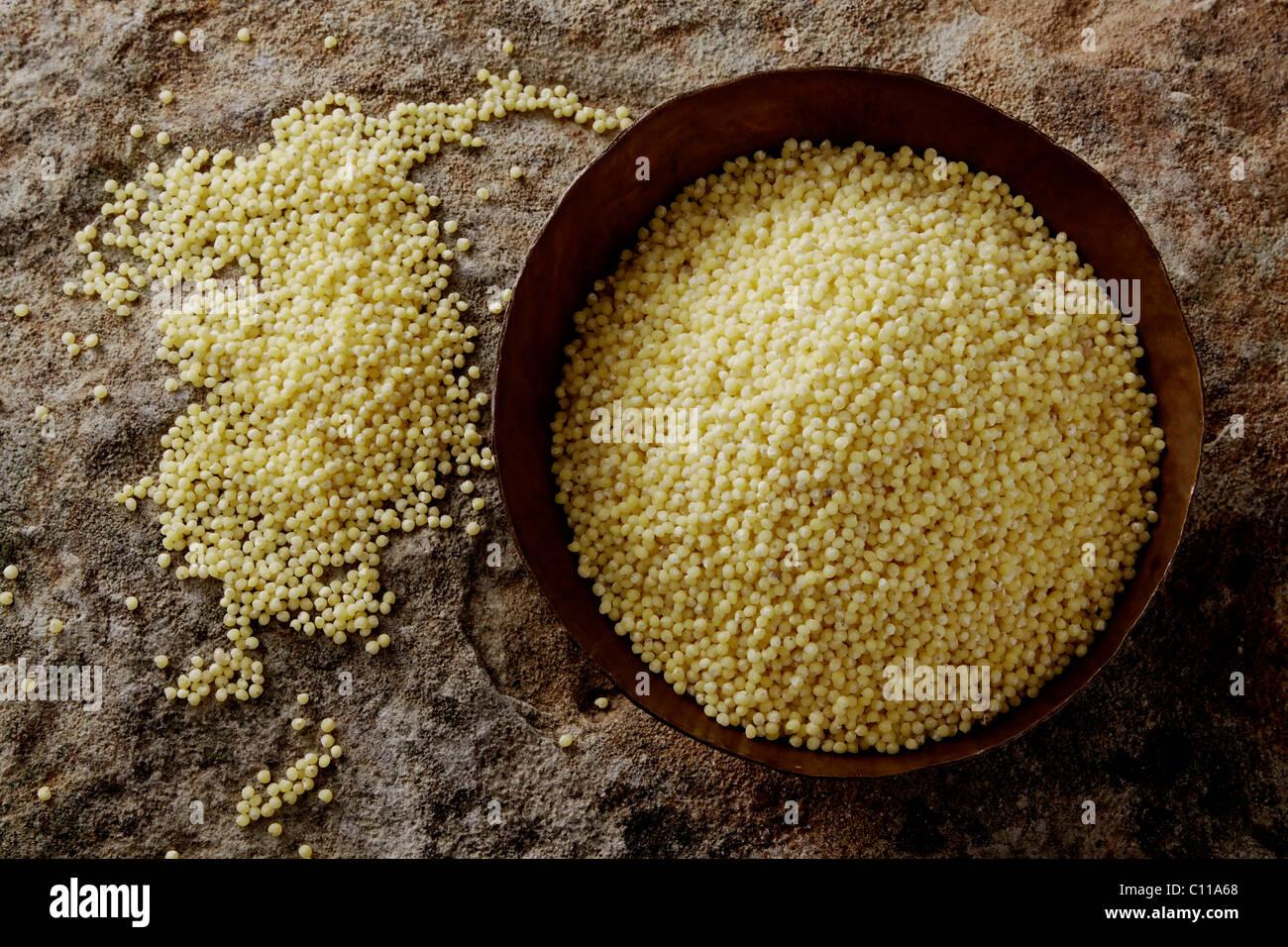 Millet (Panicum miliaceum) dans un bol de cuivre sur une surface en pierre Photo Stock