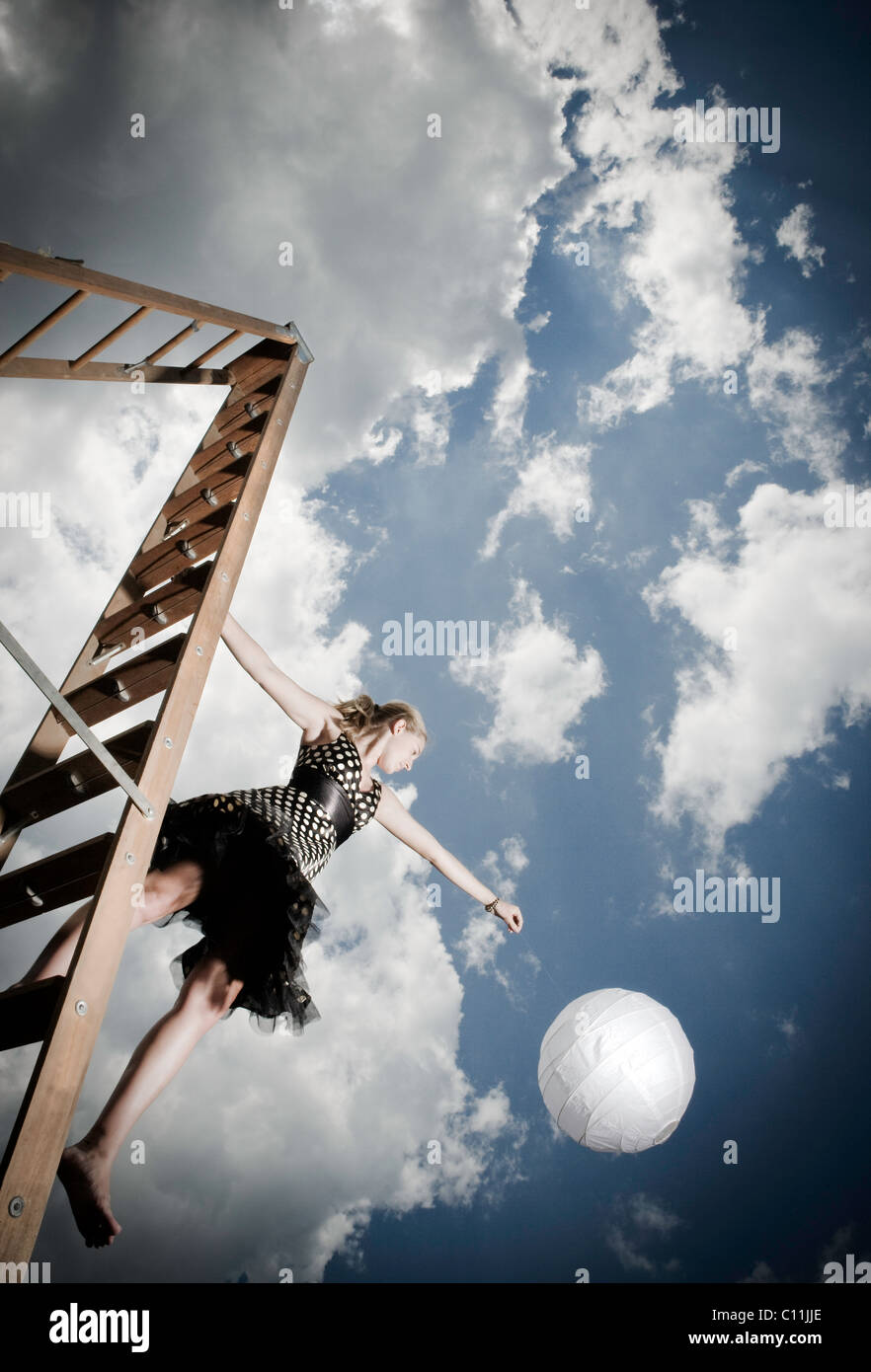 Une jeune fille portant un noir et blanc polka dotted dress se dresse sur une échelle tout en tenant une boule Photo Stock