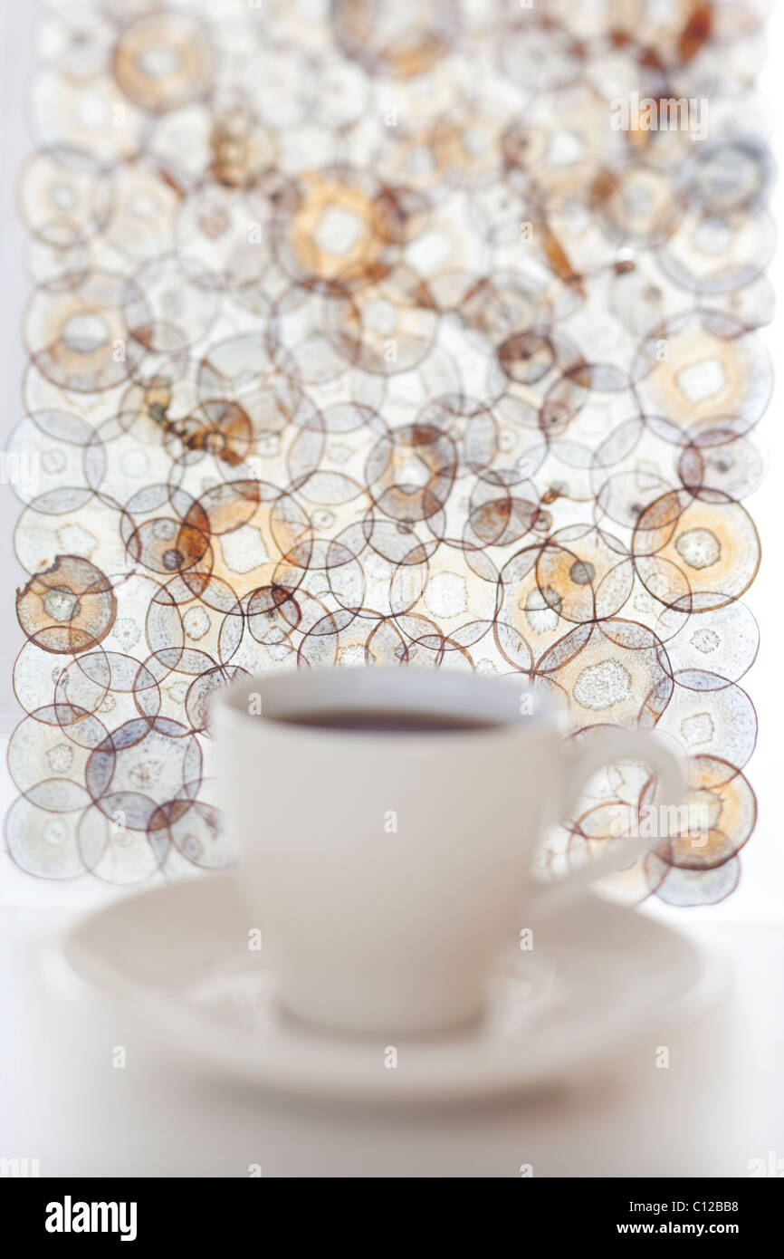 Tasse de thé hors foyer avec modèle circulaire derrière elle Photo Stock