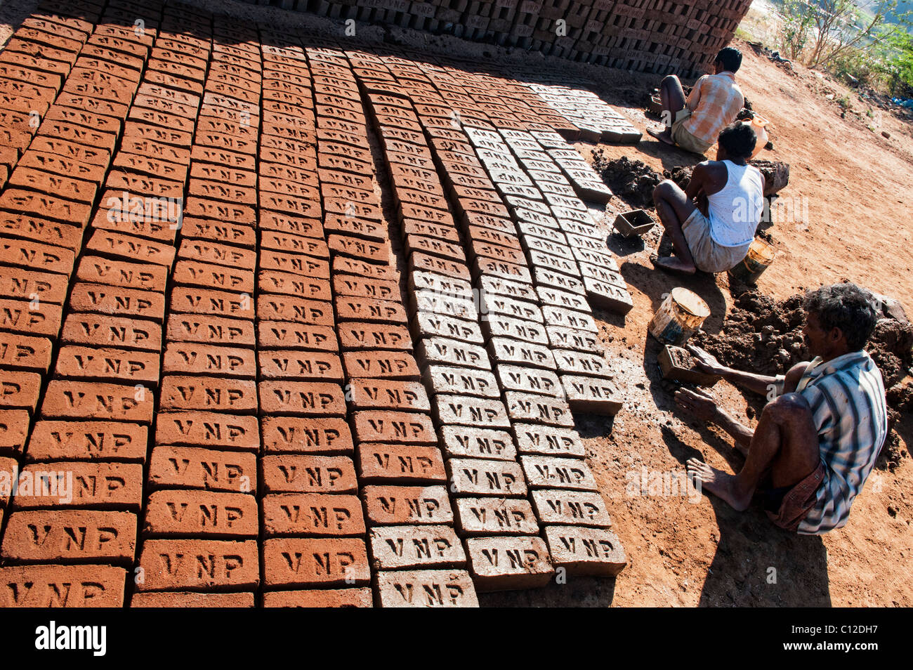 Les hommes indiens maison de briques à la main à l'aide d'un moule et de l'argile humide / Photo Stock