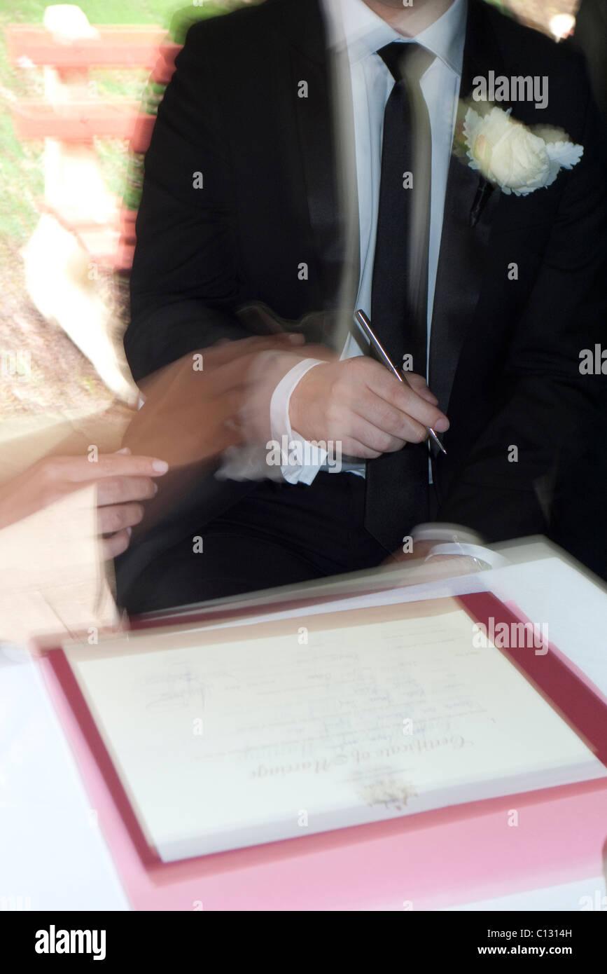 La signature du certificat de mariage marié guidée par la mariée Photo Stock
