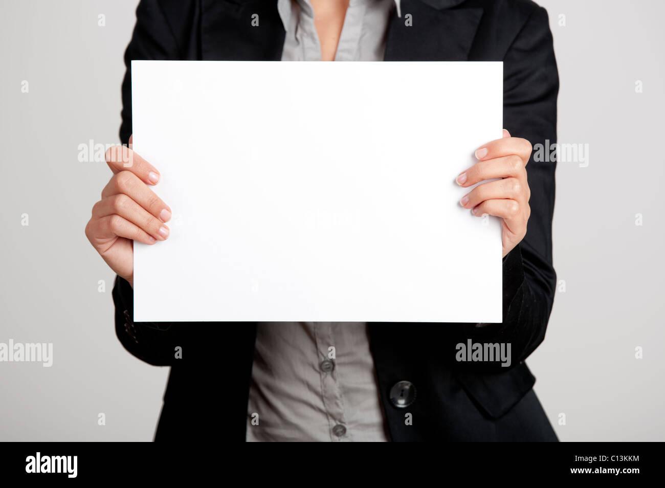 Femme tenant une feuille de papier vierge avec les deux mains Banque D'Images