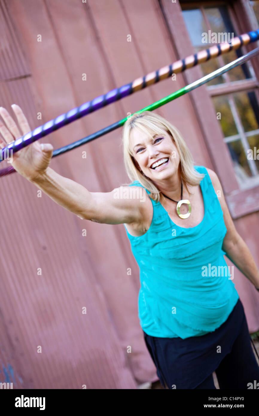 Une femme mature étend son bras faisant du hula hoop exerce à Chelsea, New York. Photo Stock