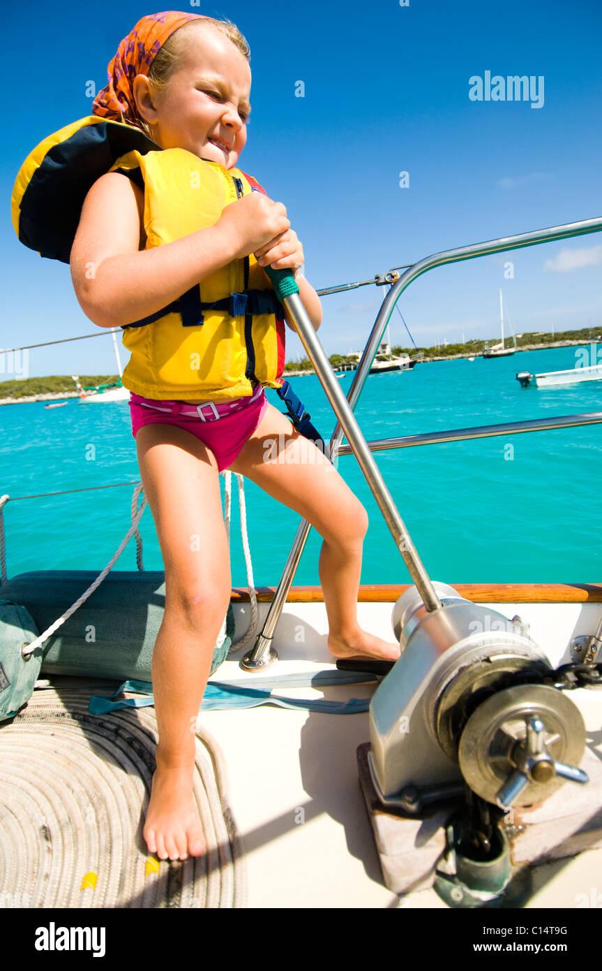 Une jeune fille aide à mettre en place l'ancre avant qu'une journée en mer avec sa famille Photo Stock
