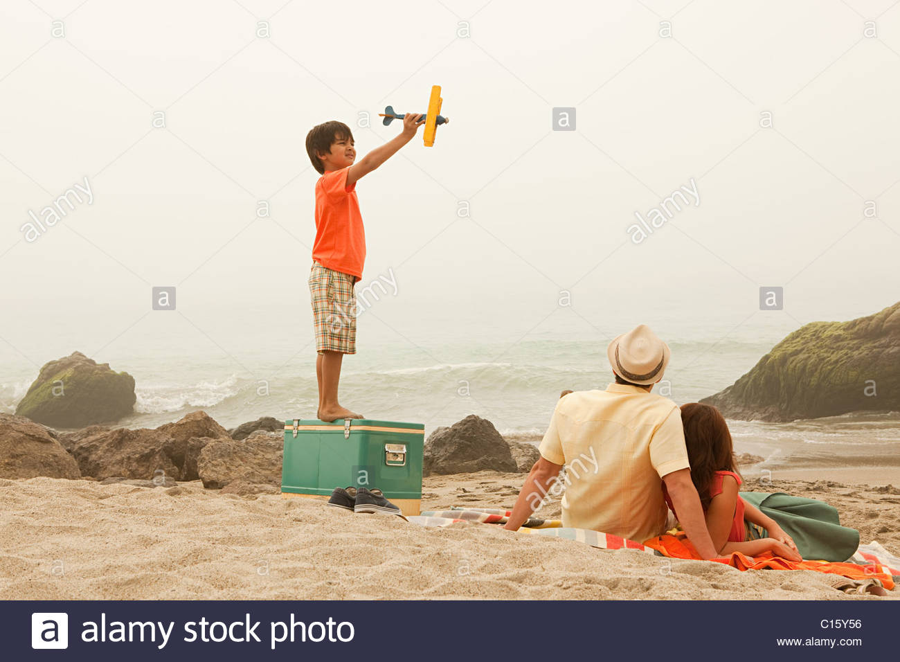 Family on beach, boy playing with toy plane Photo Stock