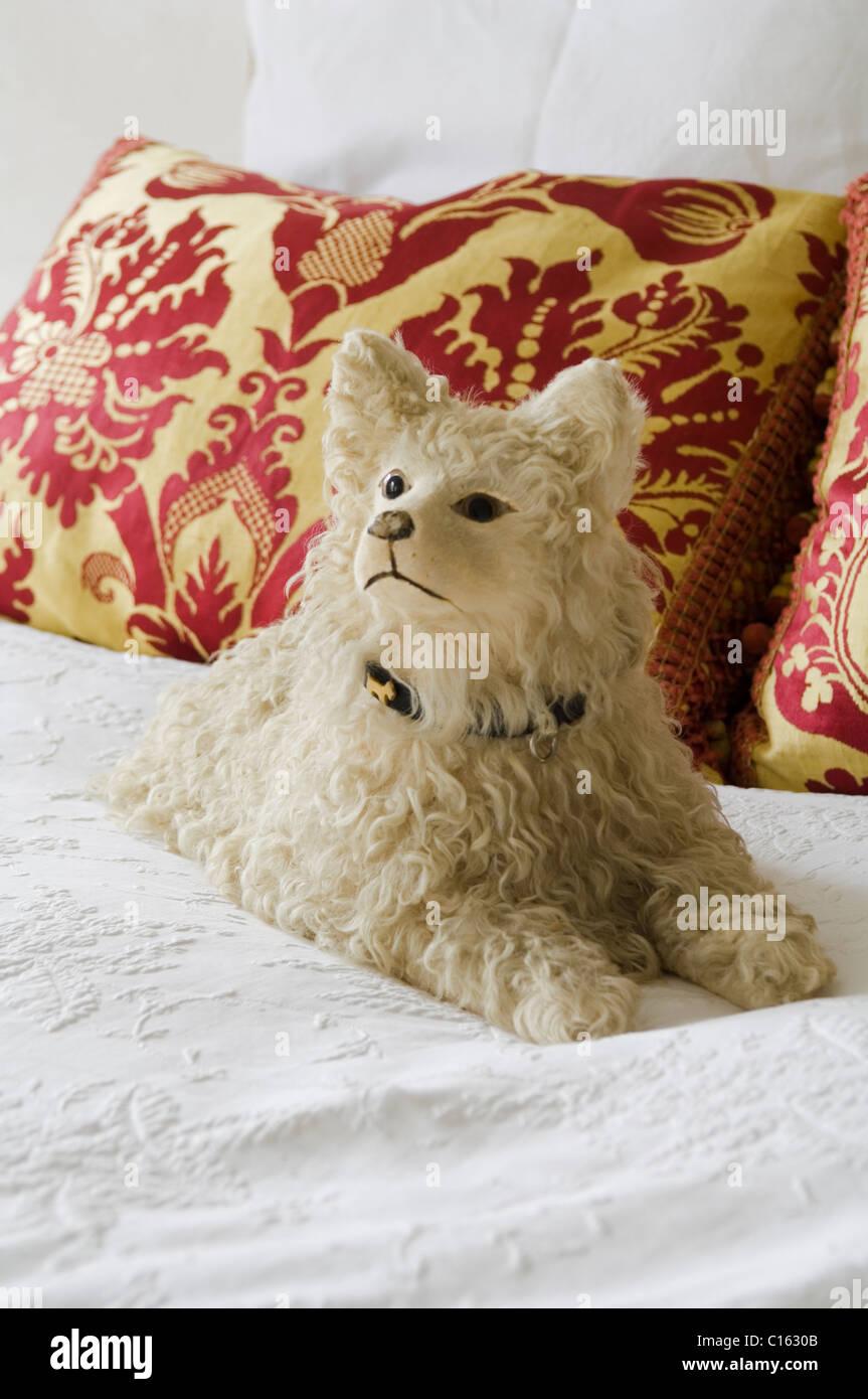 Chien en peluche jouet sur des draps blancs avec des coussins à motifs baroques Photo Stock