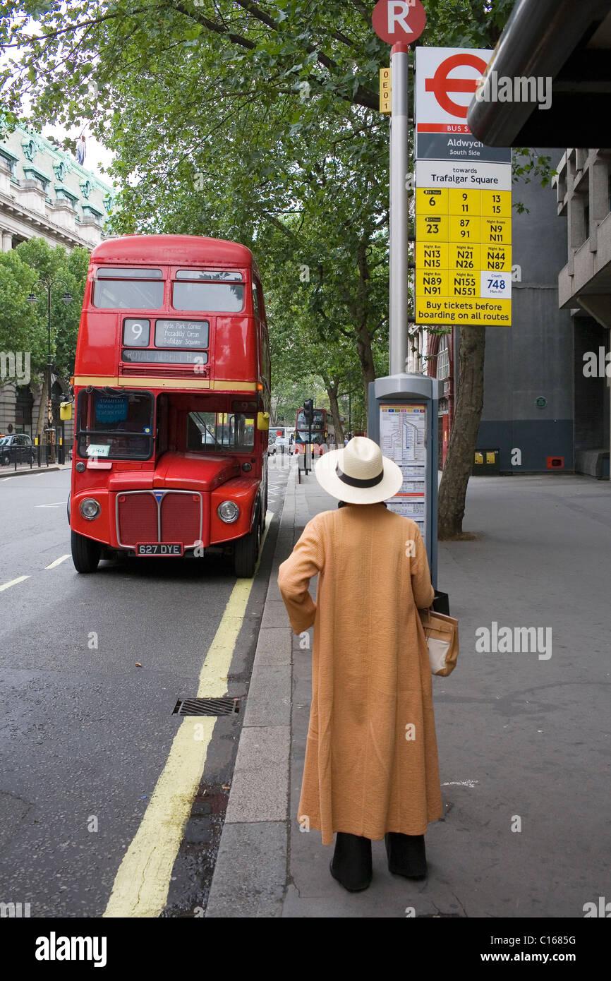 bac807ad5db une-femme-dans-un-long -manteau-brun-et-blanc-hat-attend-un-bus-routemaster-rouge-a-larret-sur-le-brin-dans-le-centre-de-londres-au-royaume-uni-c1685g.jpg