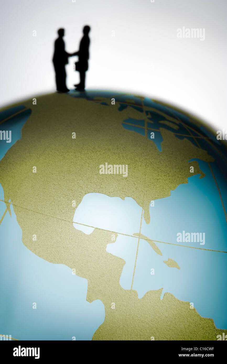 Des figurines de serrer la main au sommet d'un globe de verre coloré dans un concept d'affaires international Photo Stock