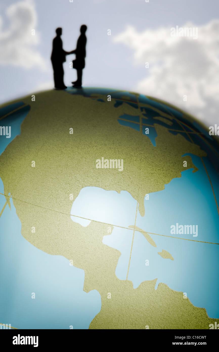 Des figurines de serrer la main au sommet d'un globe de verre coloré dans un concept d'affaires international de Banque D'Images