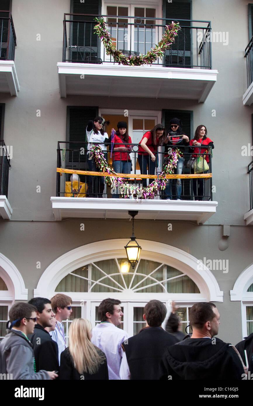 Les femmes sur un balcon flirter et pierres colliers Mardi Gras à foule d'hommes ci-dessous sur Bourbon Photo Stock