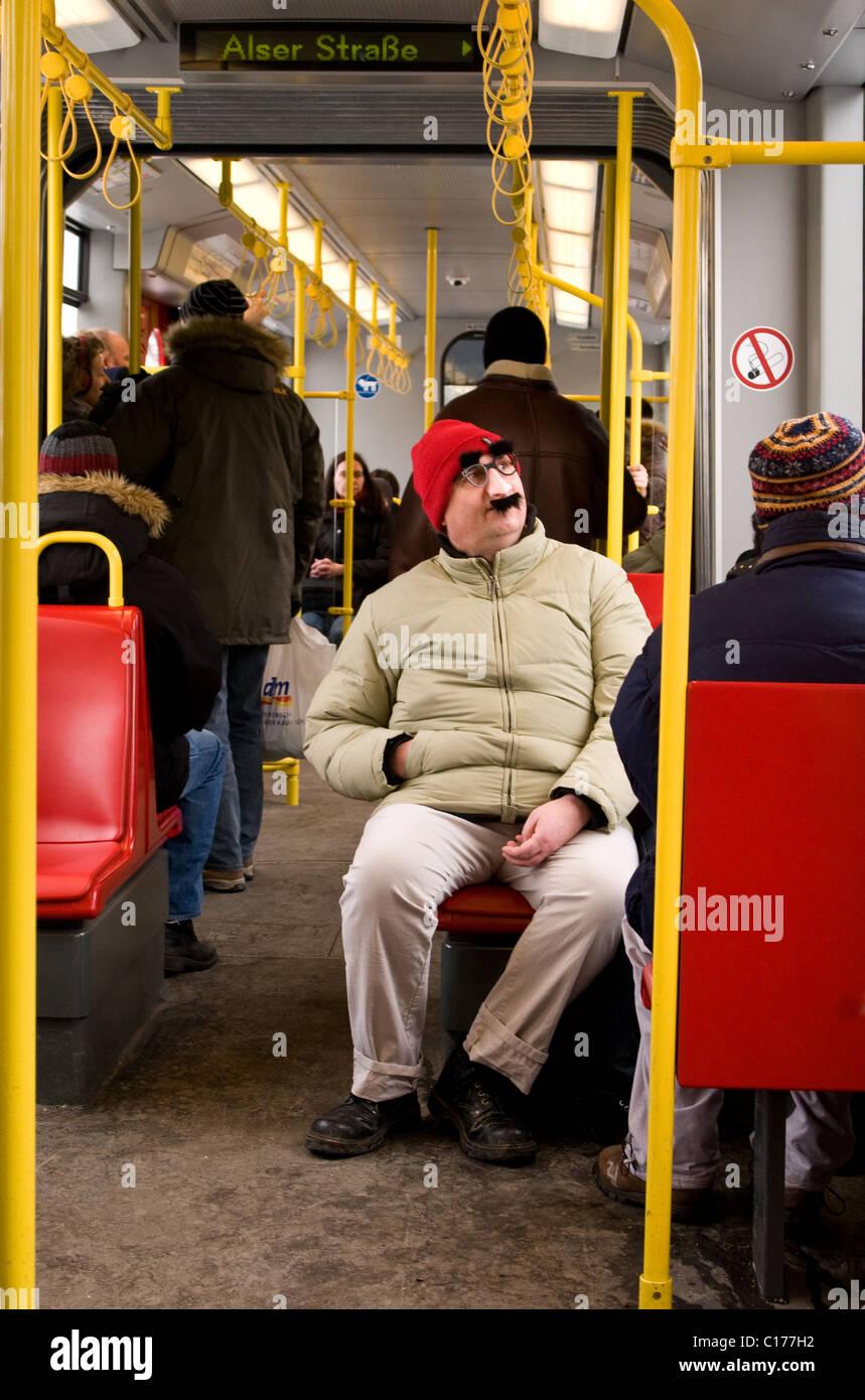 Siège passager dans le métro dans un kit de déguisement et red hat. Photo Stock
