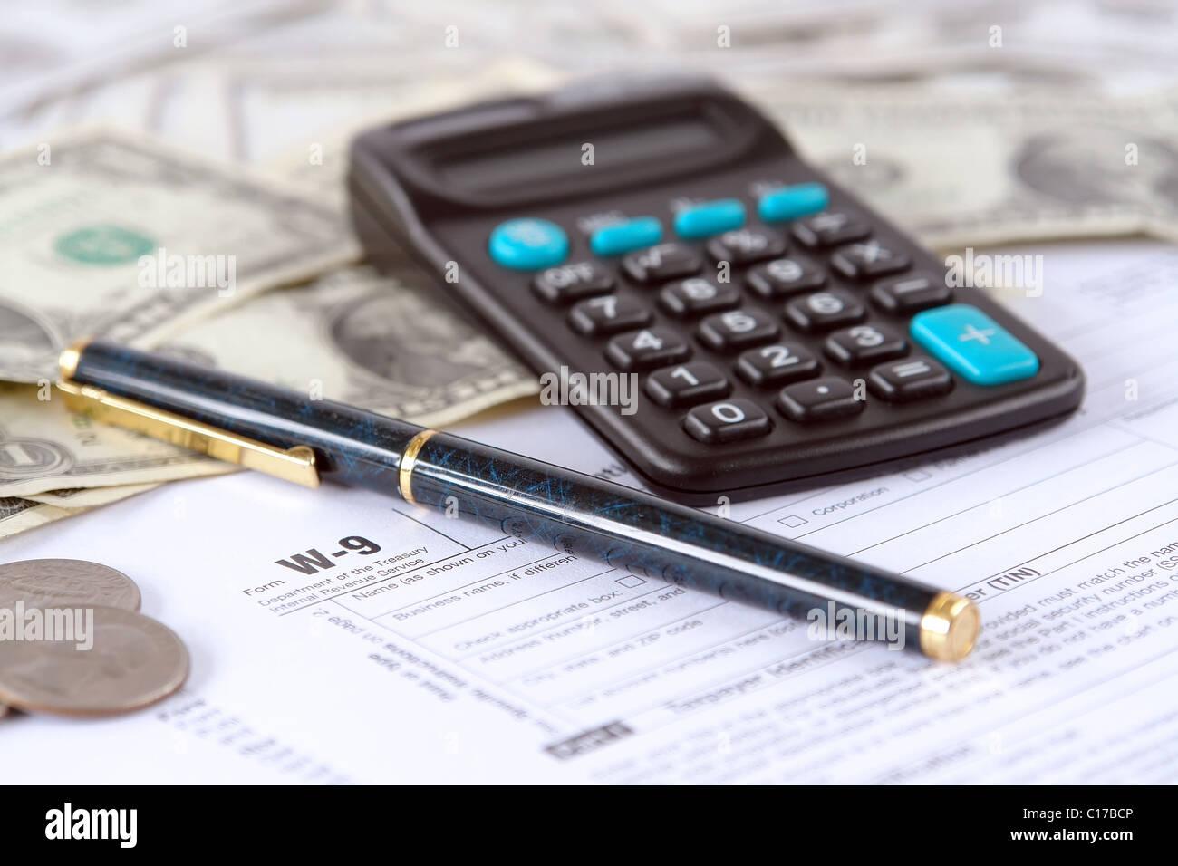 Blank W-9 Formulaire d'impôt sur le revenu avec un stylo, calculatrice et dollars américains Photo Stock